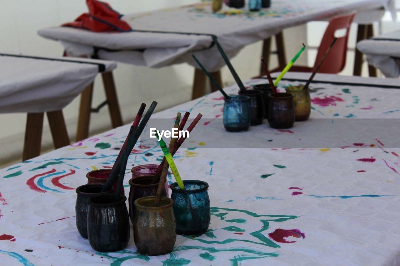 table, indoors, art and craft, paintbrush, brush, container, no people, focus on foreground, craft, still life, paint, messy, multi colored, creativity, watercolor paints, close-up, day, absence, art and craft equipment, choice