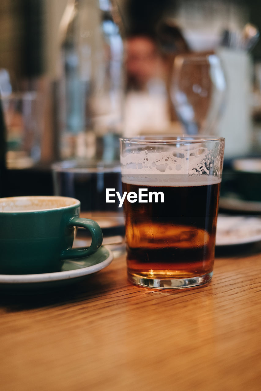 drink, refreshment, food and drink, table, drinking glass, household equipment, alcohol, glass, still life, mug, indoors, cup, focus on foreground, close-up, wood - material, coffee, coffee - drink, freshness, coffee cup, no people, frothy drink, crockery, bar counter