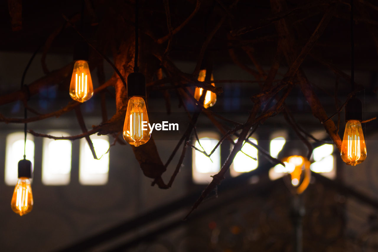 Close-Up Of Illuminated Light Bulbs Hanging At Home