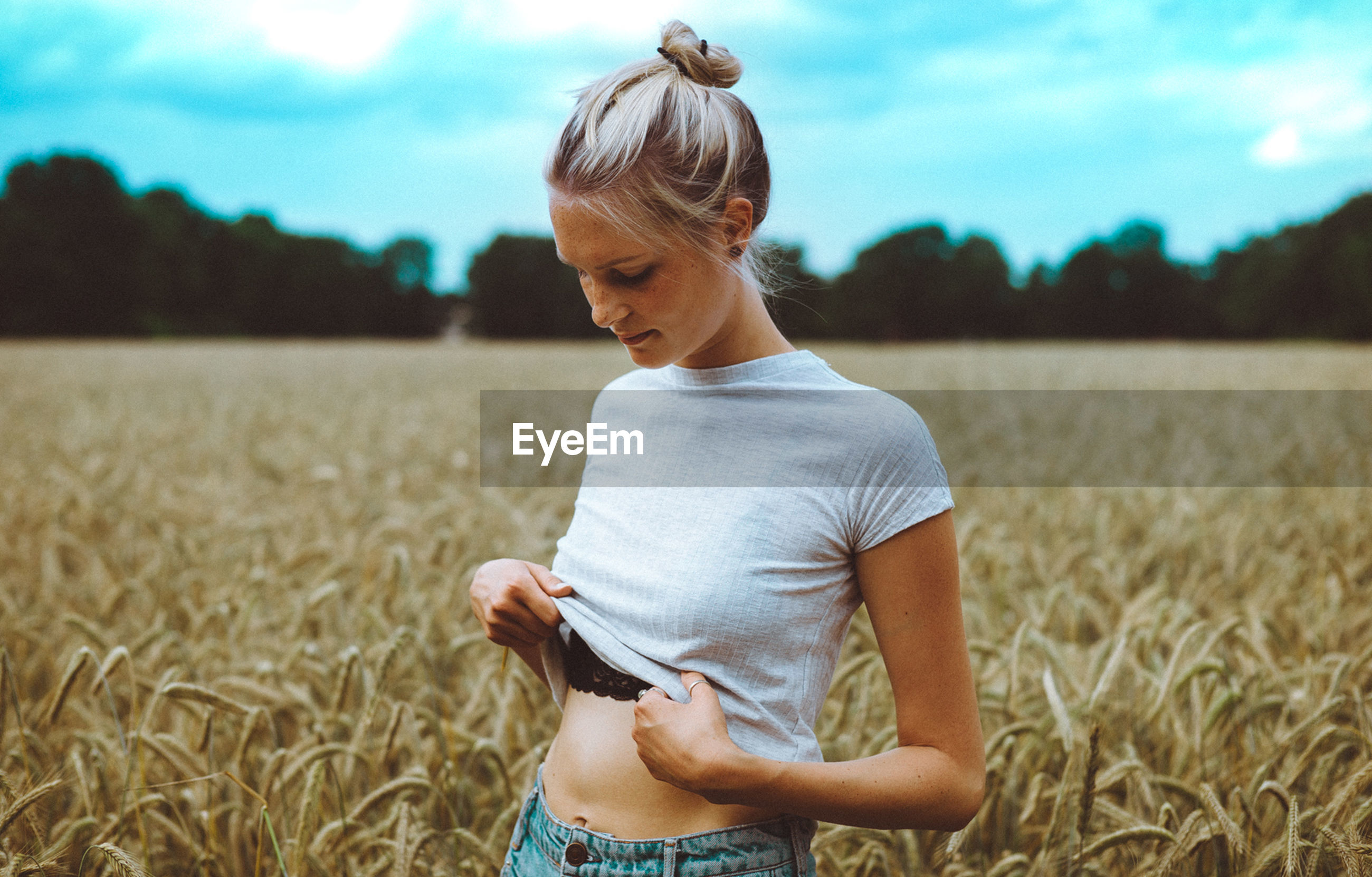 GIRL STANDING ON GRASSY FIELD