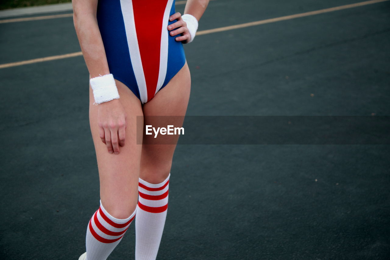 Midsection Of Woman In Old-Fashioned Sports Costume Standing On Track