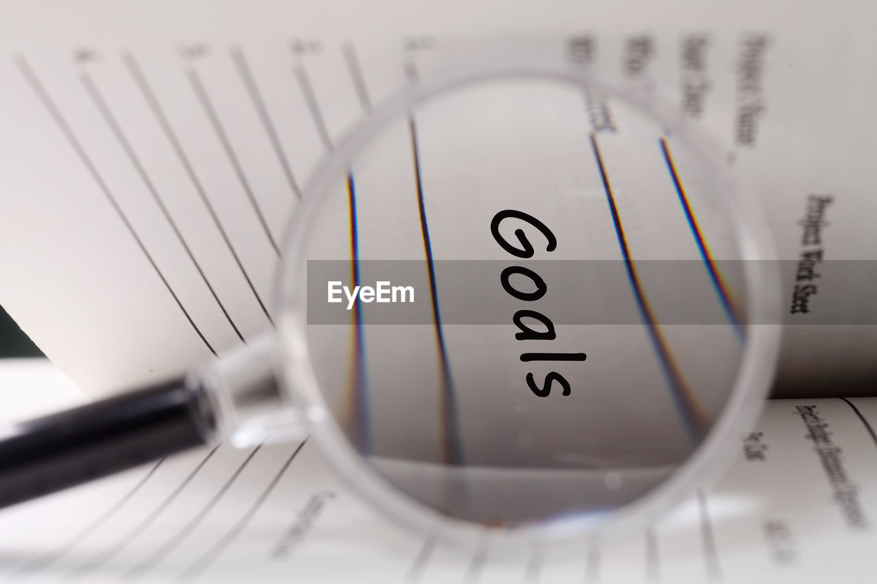 Close-up of magnifying glass showing goals text in book