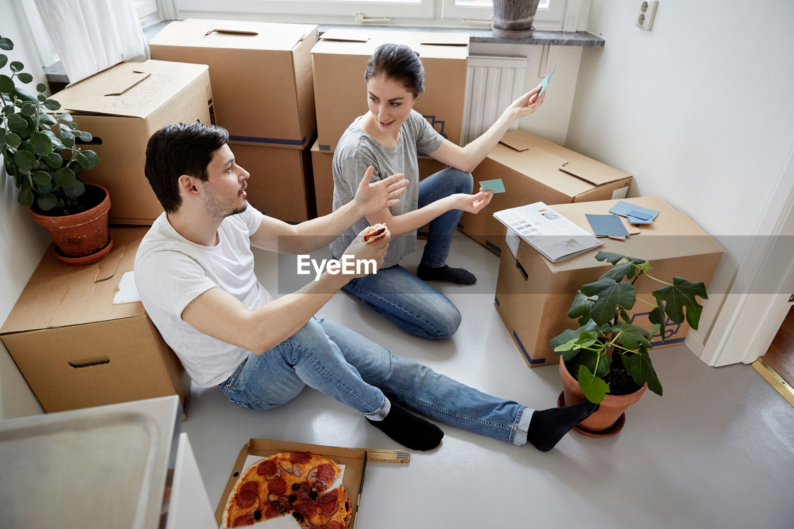 HIGH ANGLE VIEW OF COUPLE SITTING IN BOX