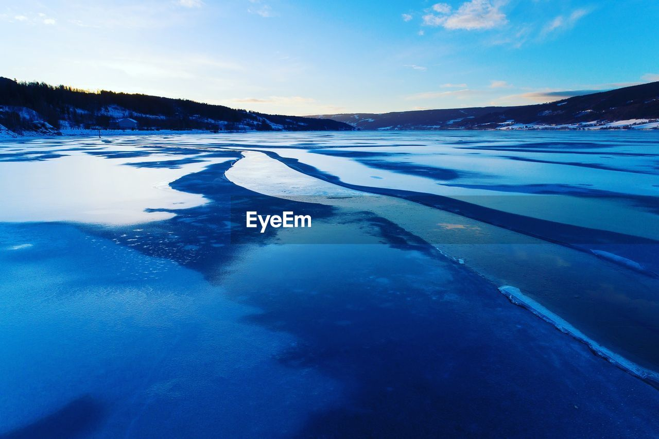 AERIAL VIEW OF FROZEN LAKE AGAINST SKY