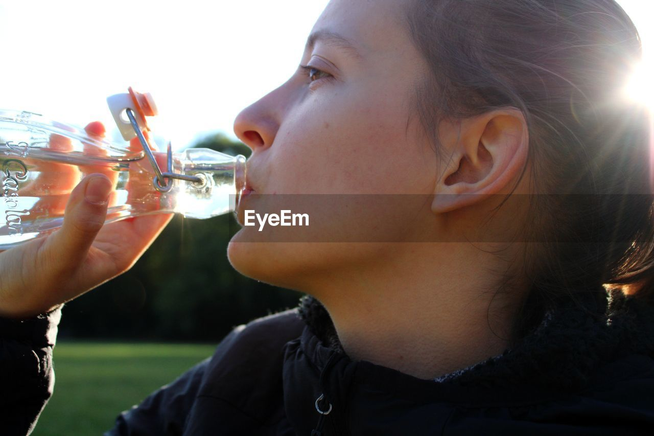 CLOSE-UP PORTRAIT OF BEAUTIFUL YOUNG WOMAN DRINKING WATER