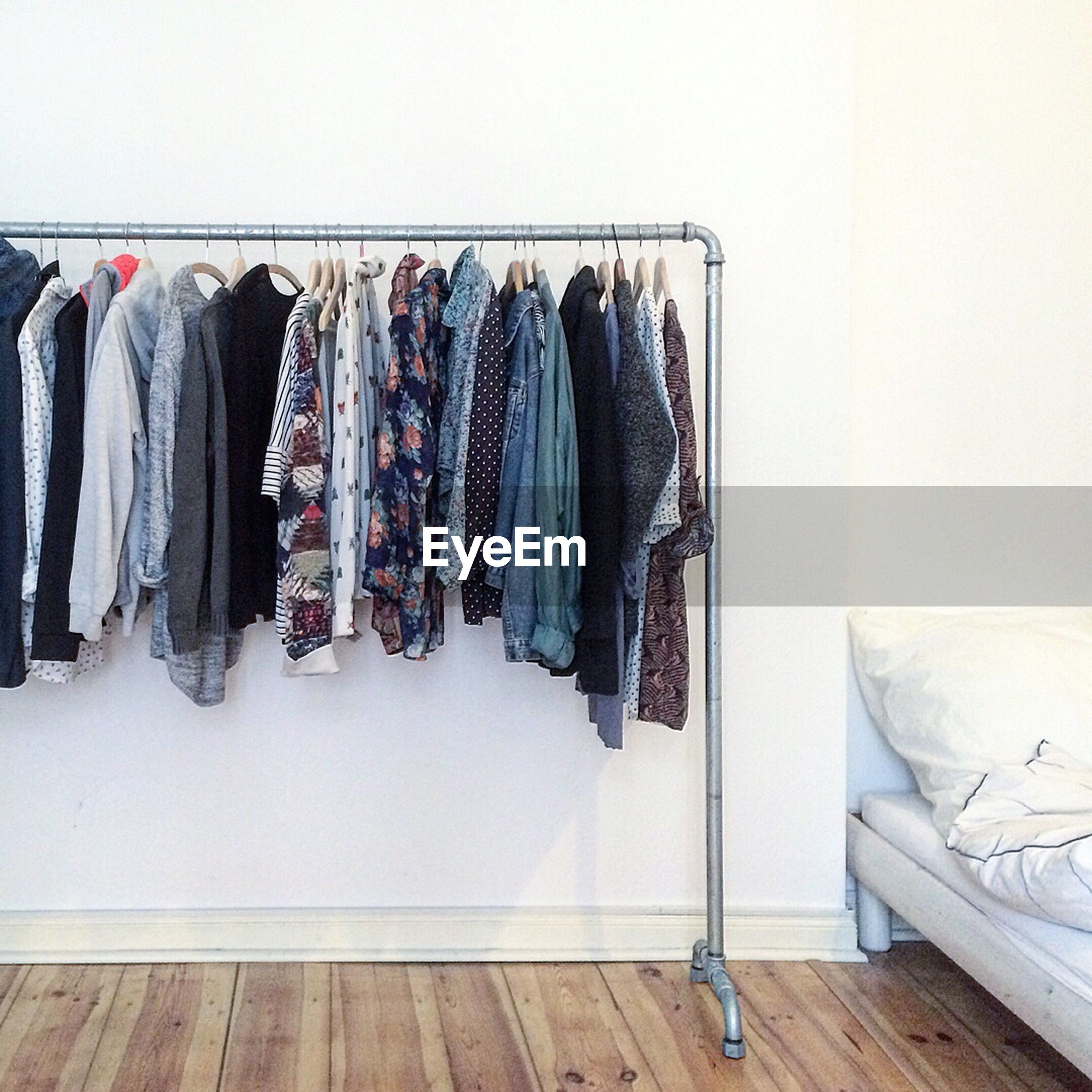 Various clothes hanging on rack against wall at home