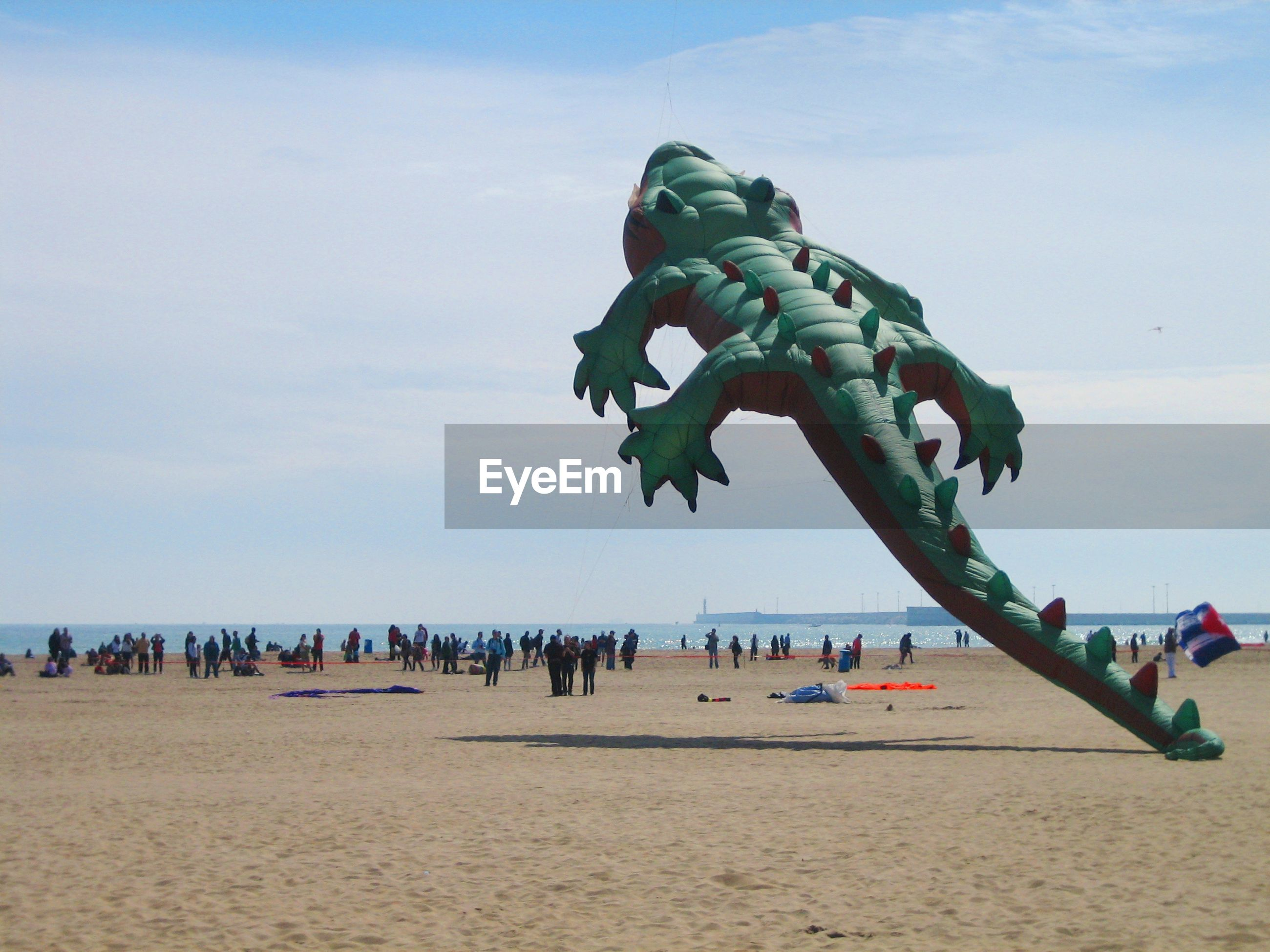 Crocodile shaped kite flying at beach during festival