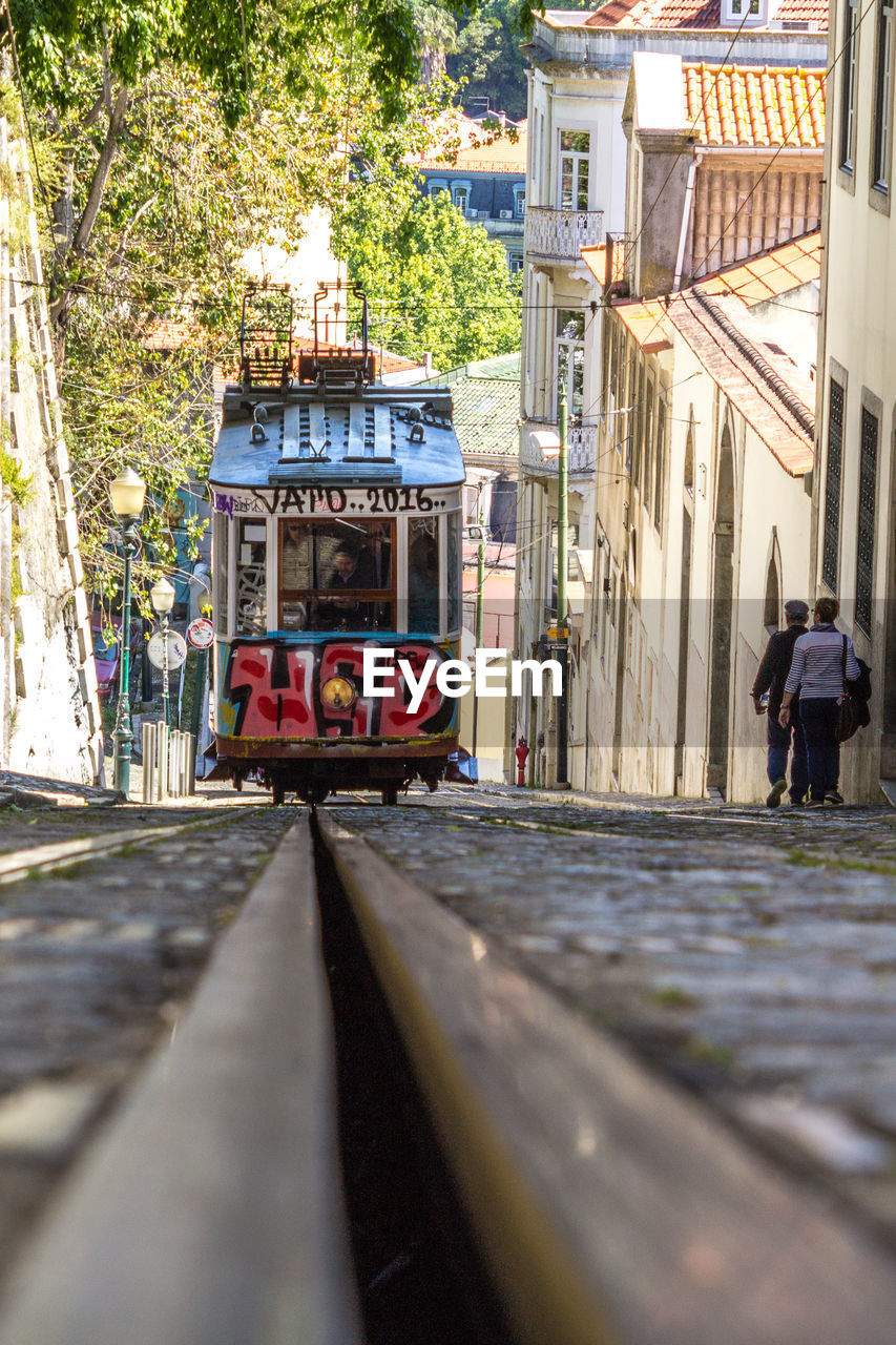 transportation, architecture, city, built structure, building exterior, mode of transportation, track, day, railroad track, incidental people, cable car, land vehicle, public transportation, rail transportation, street, nature, real people, outdoors, building, men, surface level