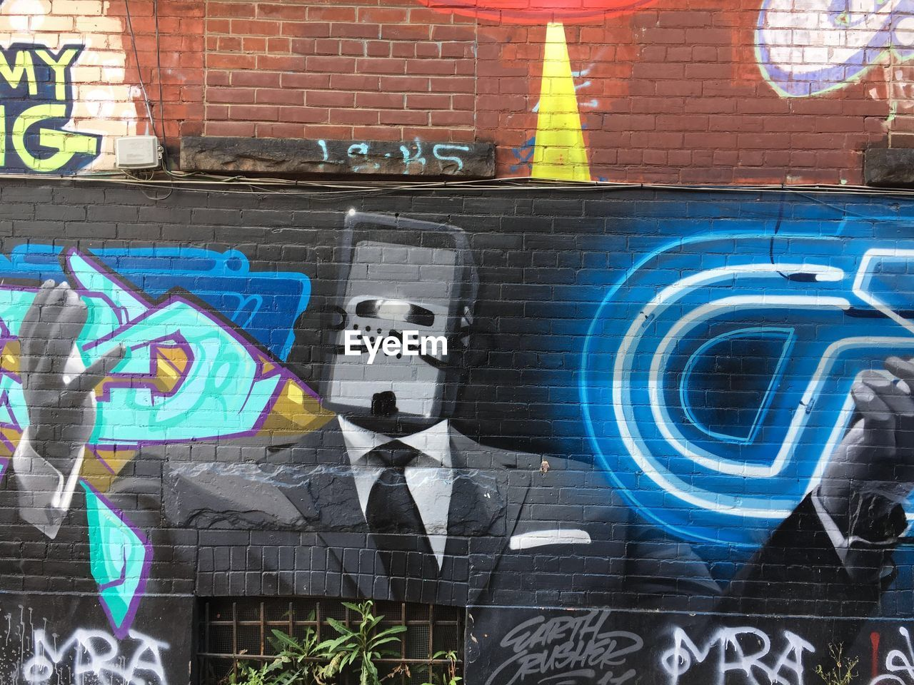 text, creativity, graffiti, western script, human representation, no people, wall - building feature, art and craft, brick wall, brick, wall, representation, architecture, communication, multi colored, day, city, built structure, building exterior, street art, outdoors, marketing, mural