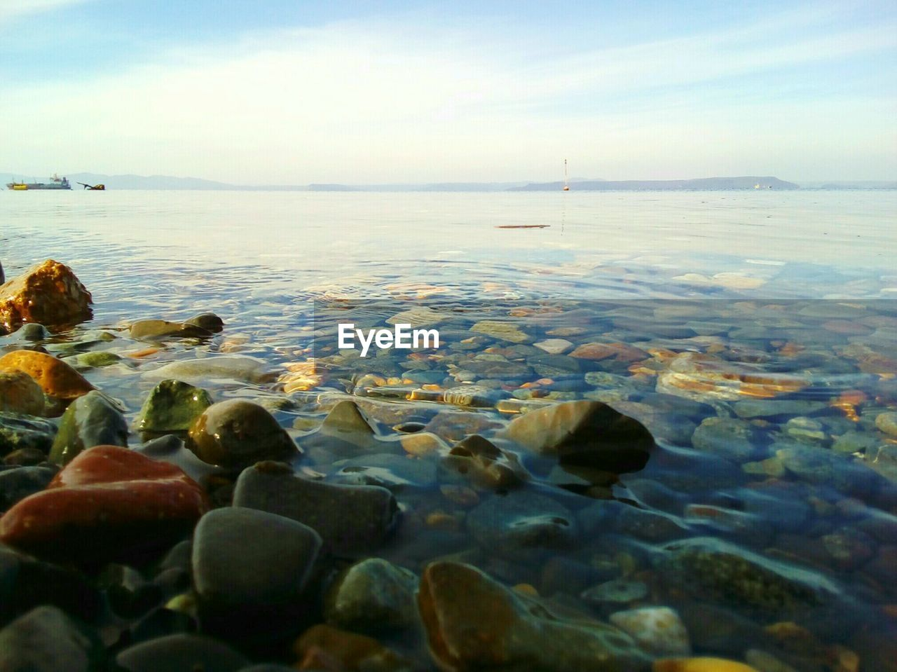 water, surface level, pebble, sea, pebble beach, nature, sky, outdoors, no people, cloud - sky, beauty in nature, tranquil scene, day, beach, scenics, horizon over water, close-up