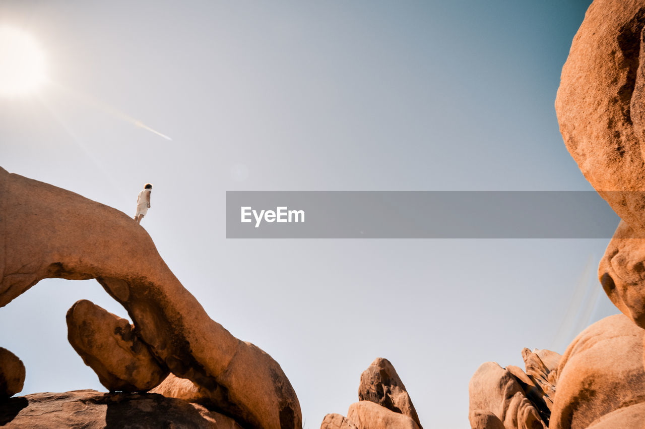 Low angle view of woman standing on rock formation against sky during sunny day
