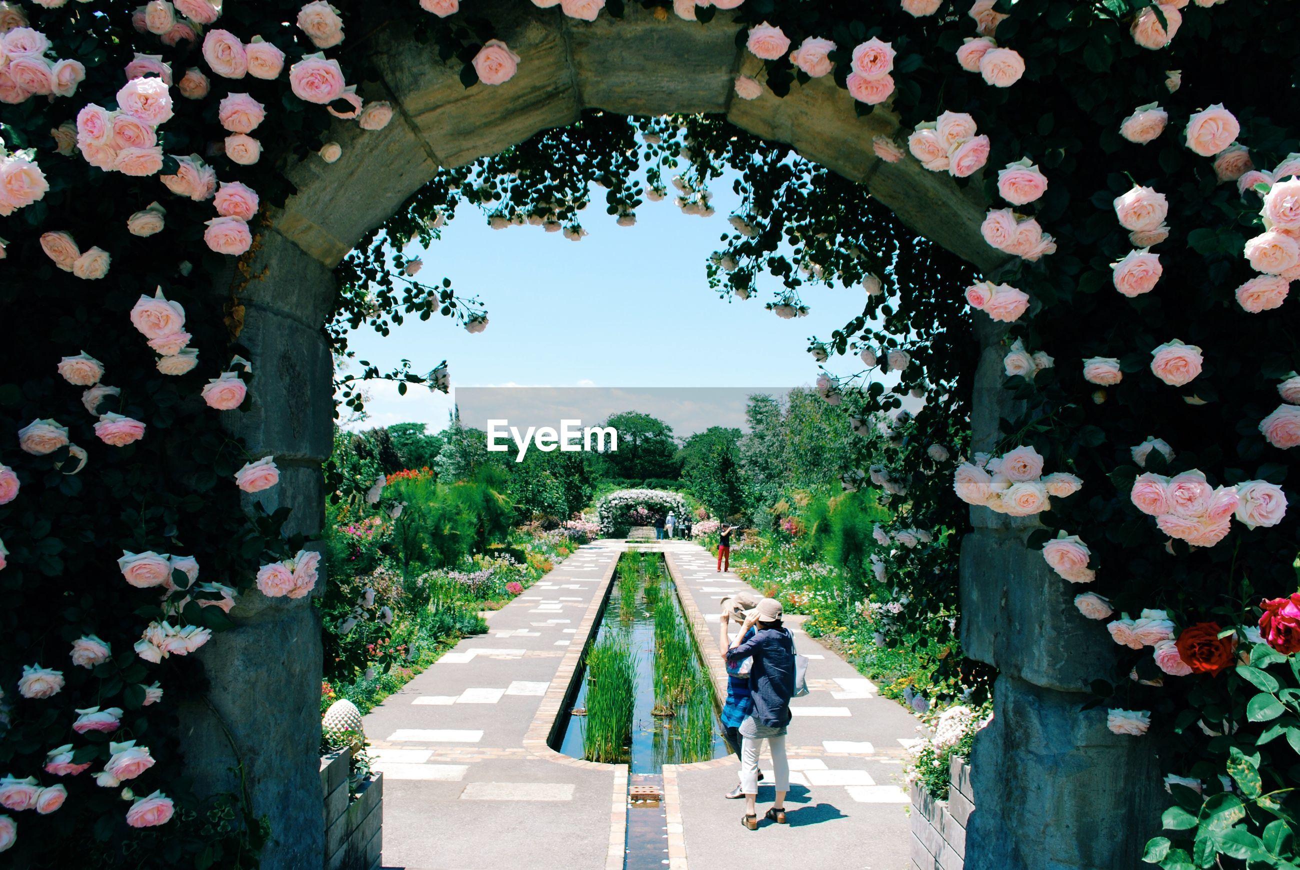 Women standing on footpath in garden seen through archway
