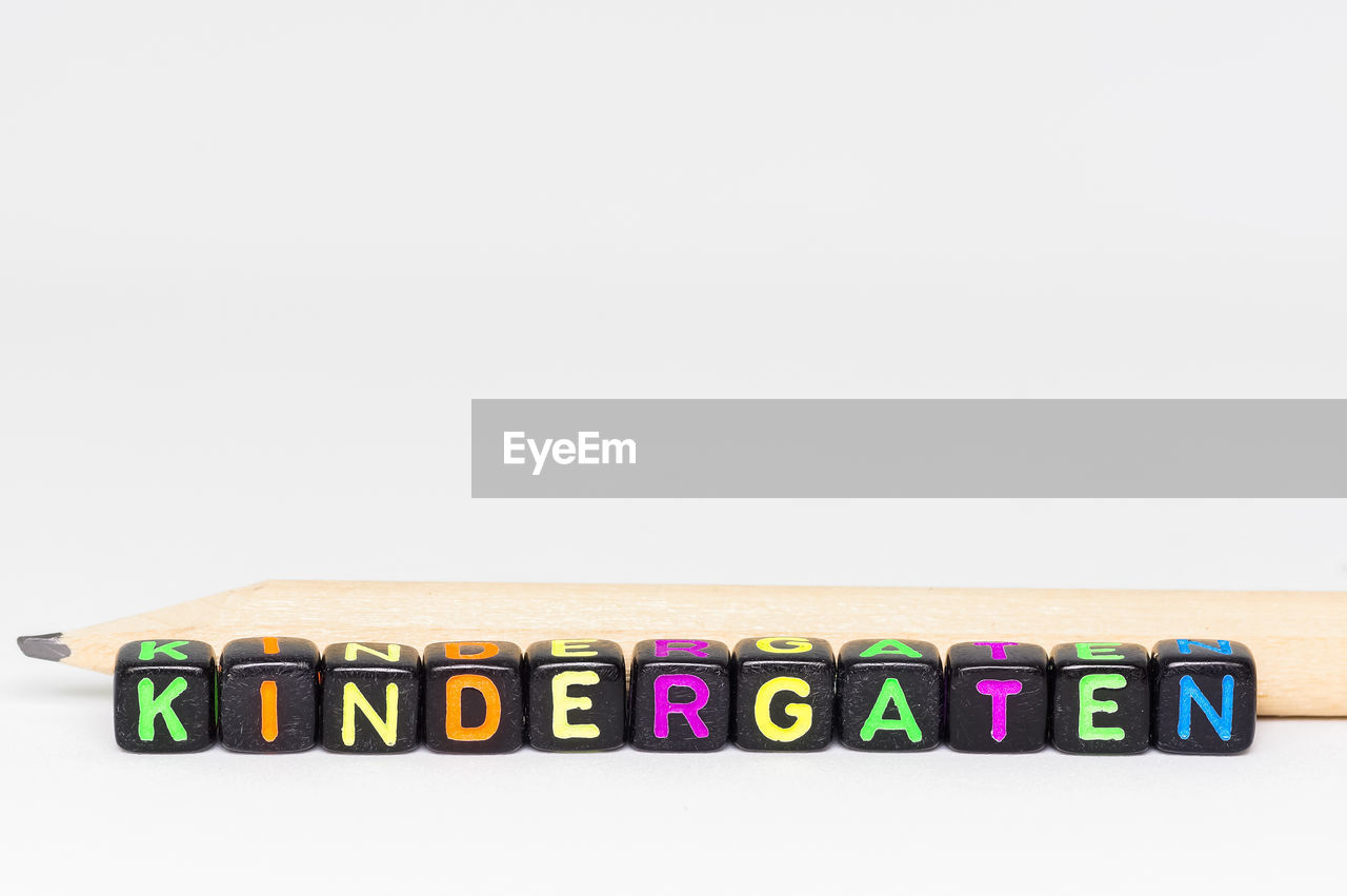 white background, studio shot, copy space, still life, wood - material, multi colored, in a row, text, communication, close-up, no people, indoors, alphabet