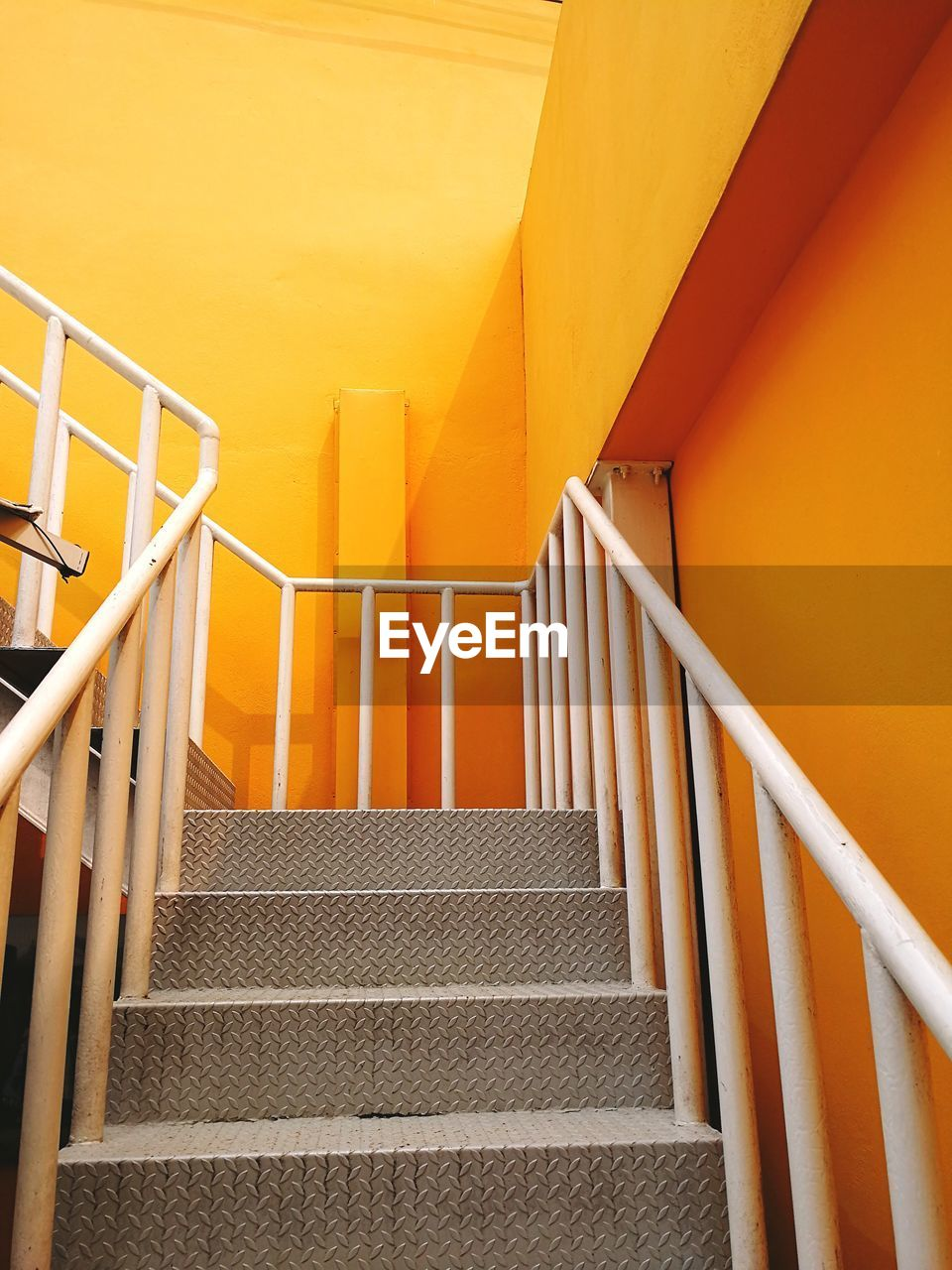 staircase, architecture, steps and staircases, railing, built structure, low angle view, yellow, no people, indoors, wall - building feature, the way forward, metal, building, pattern, day, security, direction, protection