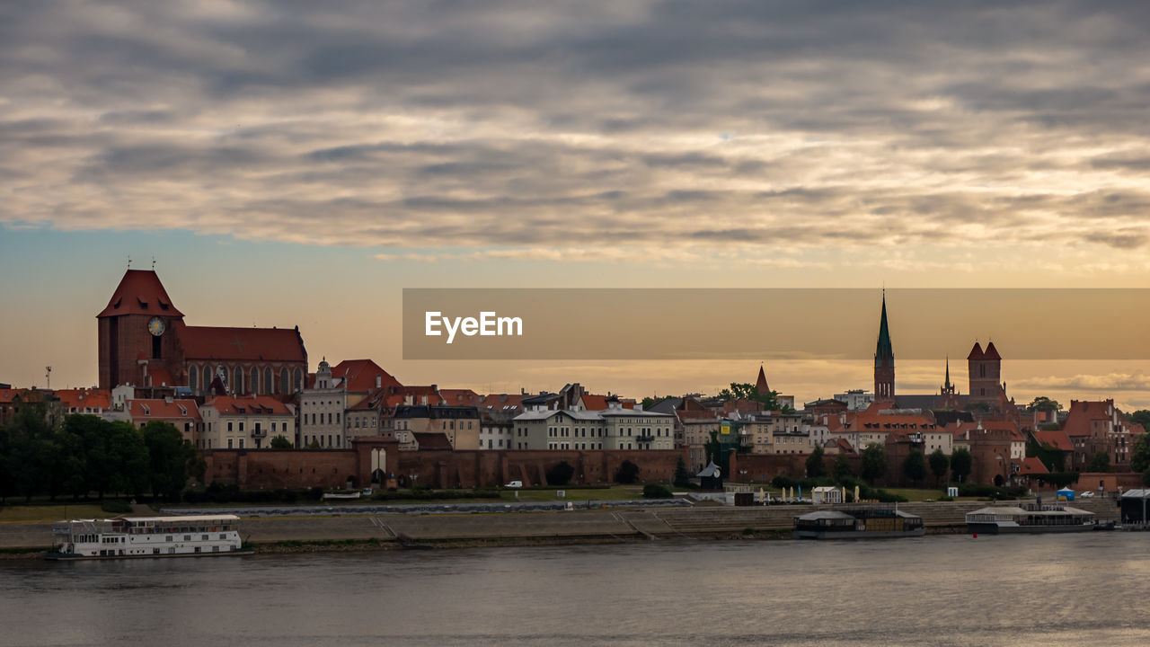 architecture, built structure, building exterior, sky, city, building, cloud - sky, sunset, water, religion, place of worship, spirituality, belief, nautical vessel, transportation, travel destinations, nature, mode of transportation, no people, cityscape, outdoors, townscape