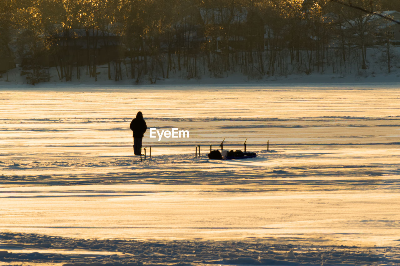 Silhouette Man Standing On Snow Covered Field During Sunset