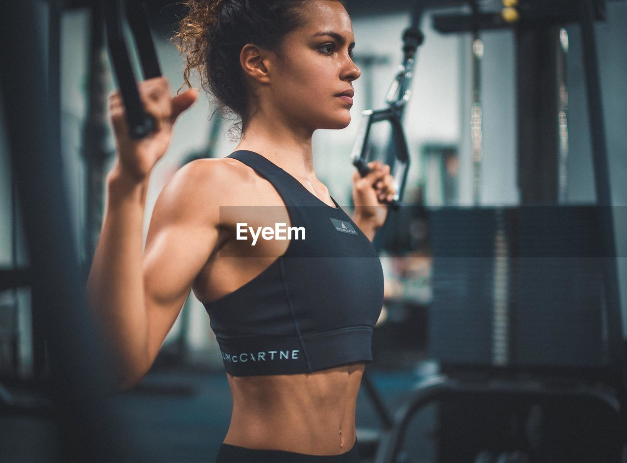lifestyles, healthy lifestyle, exercising, gym, one person, sports clothing, strength, sport, sports training, indoors, real people, young adult, determination, weight, muscular build, adult, focus on foreground, clothing, young women, weight training, body conscious, effort