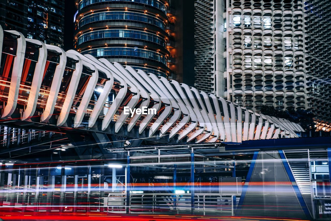 architecture, built structure, building exterior, city, illuminated, night, office building exterior, modern, transportation, building, no people, office, motion, travel destinations, travel, blurred motion, long exposure, tall - high, skyscraper, outdoors, financial district