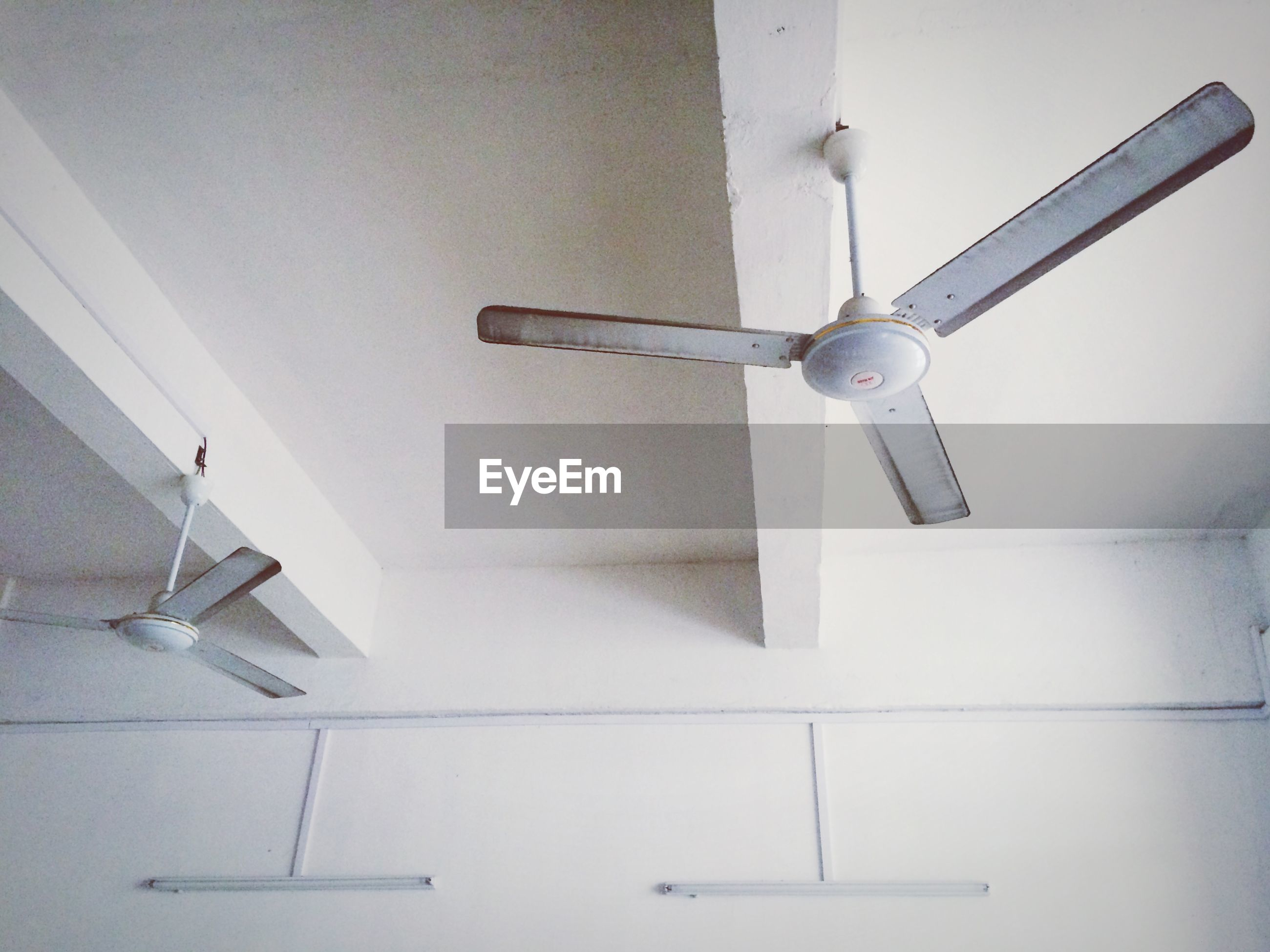 indoors, architecture, low angle view, built structure, wall - building feature, ceiling, lighting equipment, white color, technology, no people, wall, home interior, white, modern, hanging, electric lamp, electricity, airplane, lamp, day