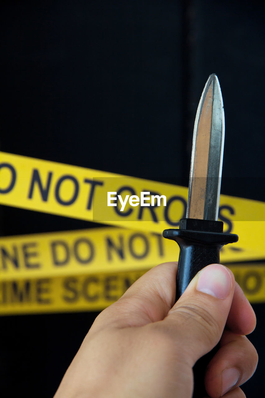 Close-up of hand holding knife against cordon tape