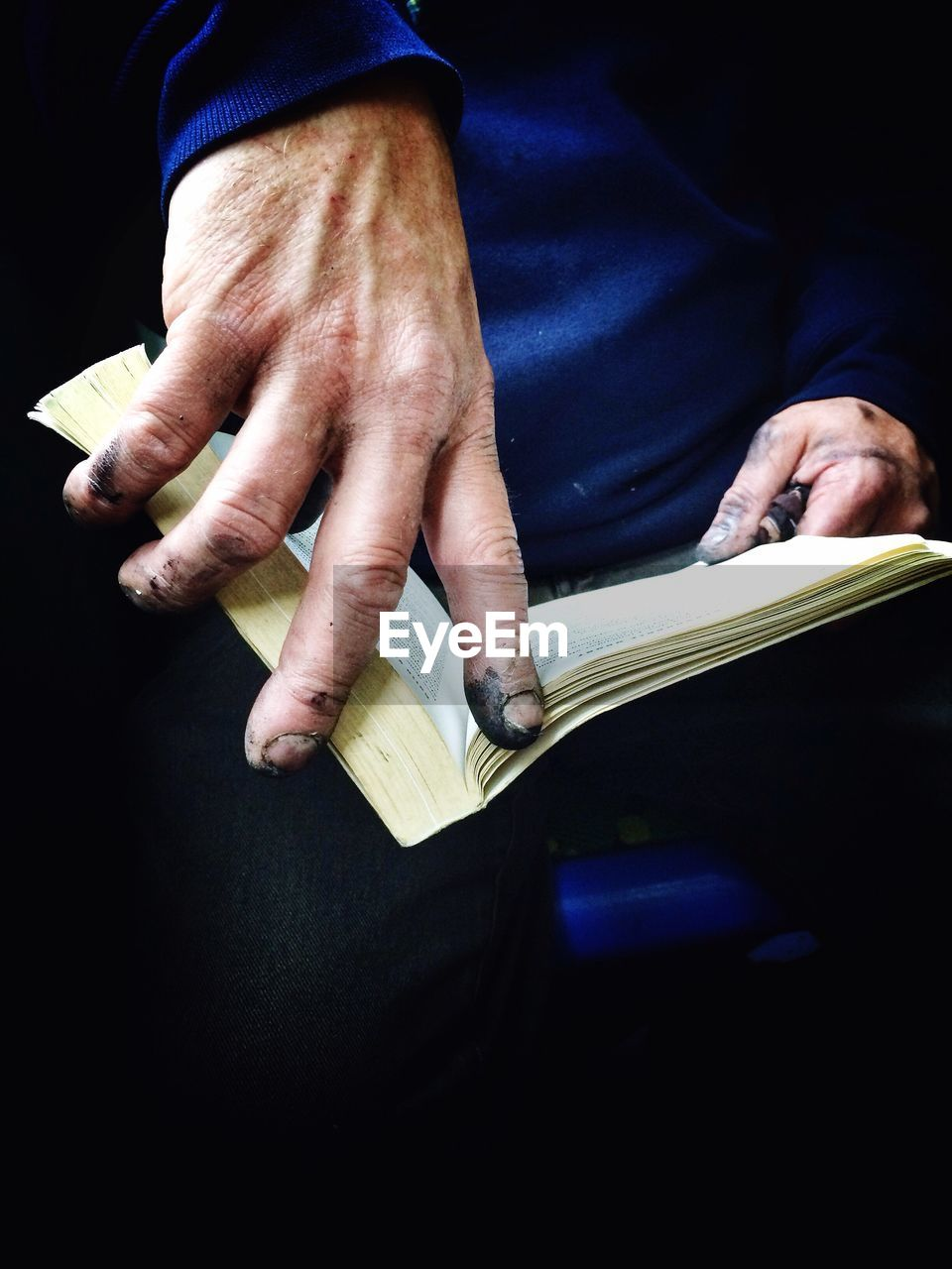 Close-Up Of Dirty Hands Holding Book
