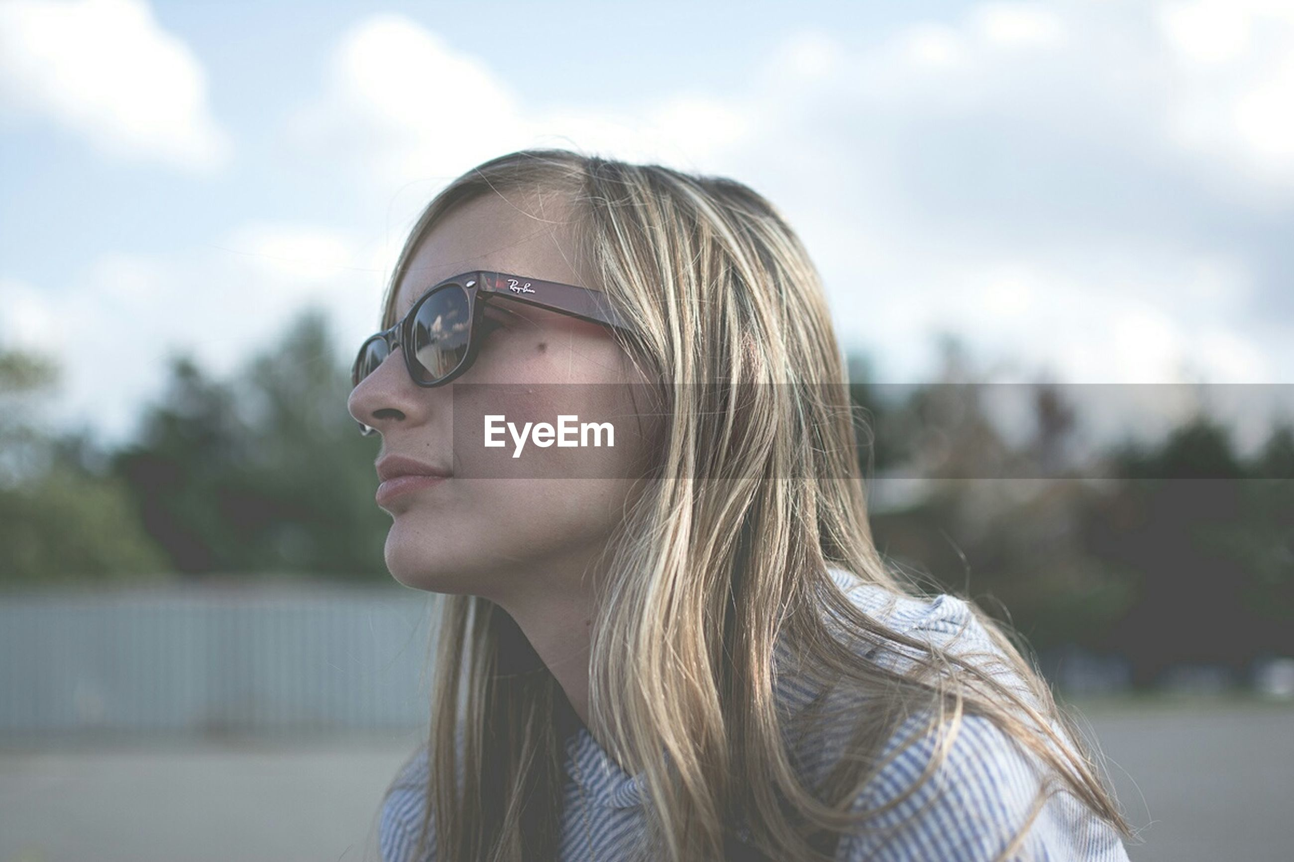 headshot, focus on foreground, young adult, lifestyles, person, young women, leisure activity, close-up, head and shoulders, portrait, front view, looking at camera, sunglasses, human face, long hair, sky, casual clothing