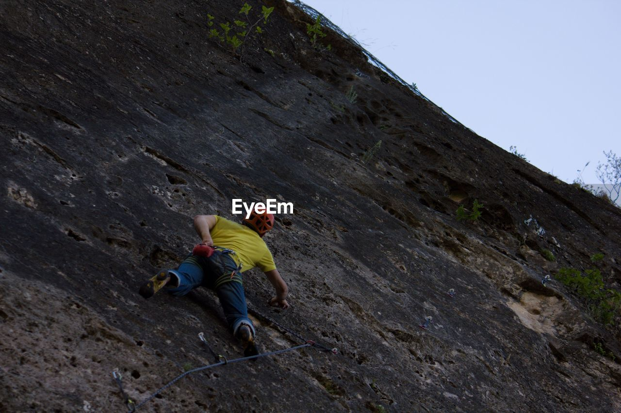 mountain, leisure activity, climbing, one person, extreme sports, full length, activity, nature, sky, sport, real people, rock, adventure, low angle view, day, rock - object, rock climbing, mountain climbing, rock formation, outdoors, effort, formation