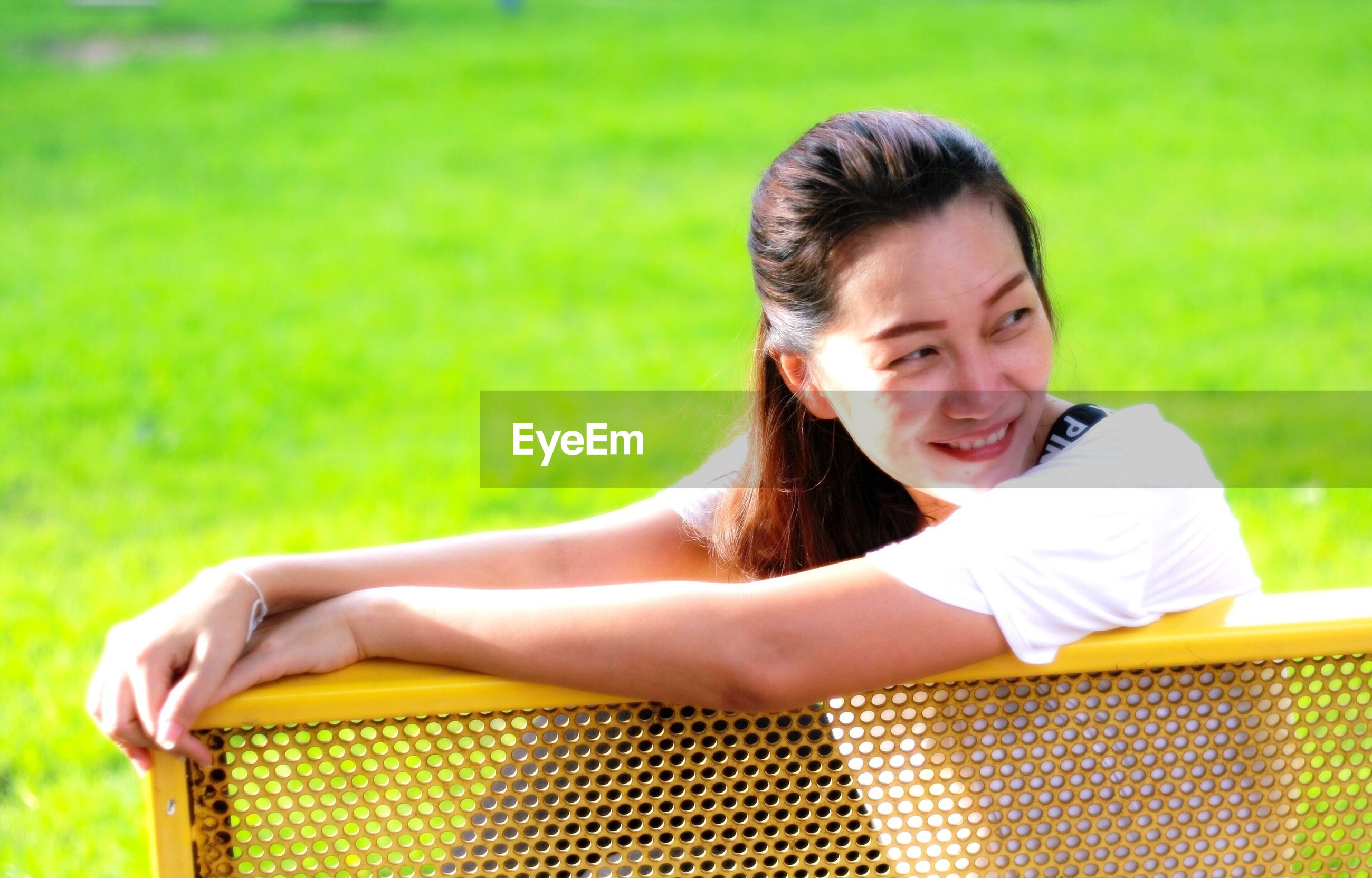 Smiling woman looking away while sitting on bench at park