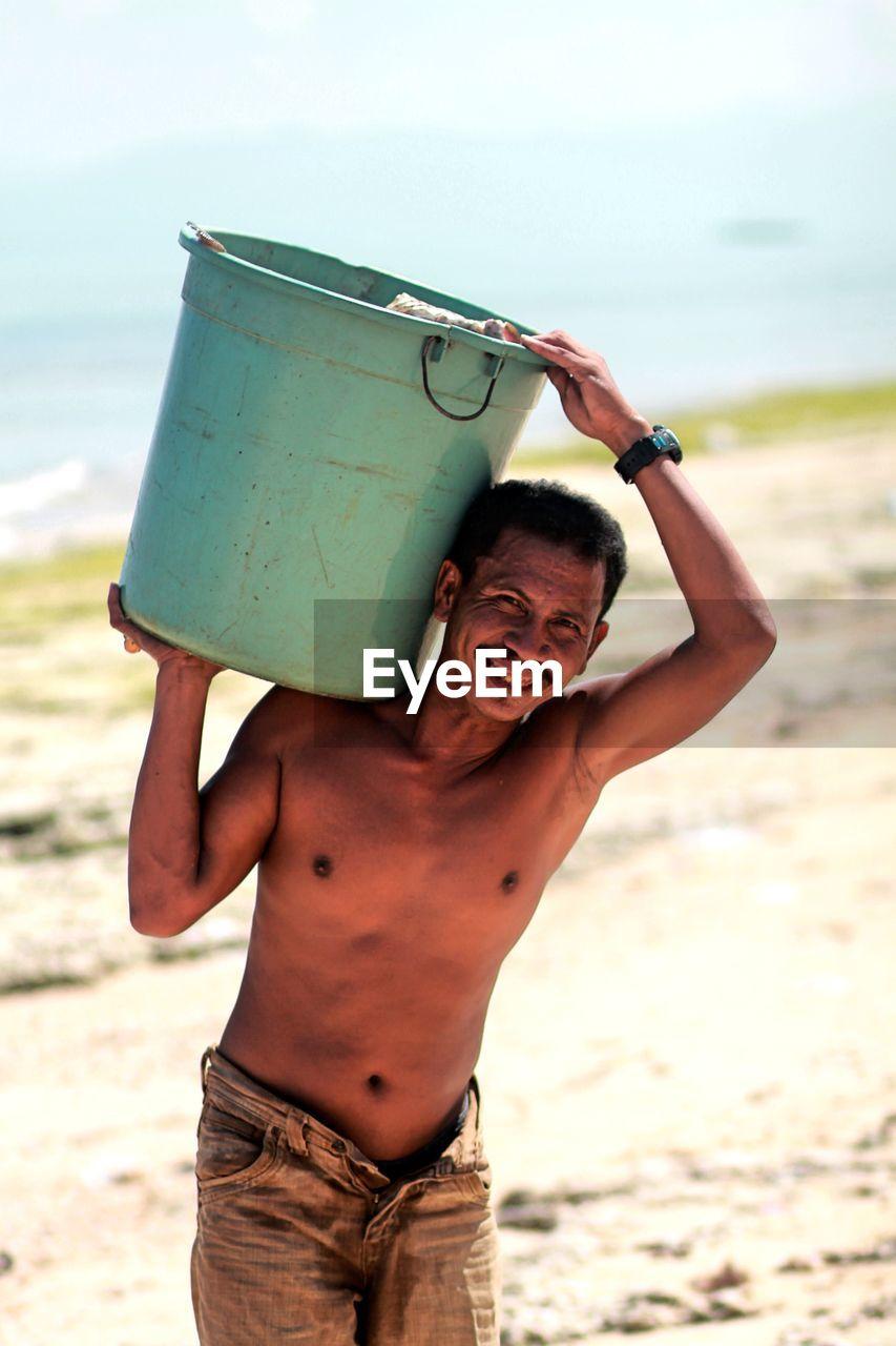 Portrait Of Smiling Man Carrying Garbage Bin On Shoulder