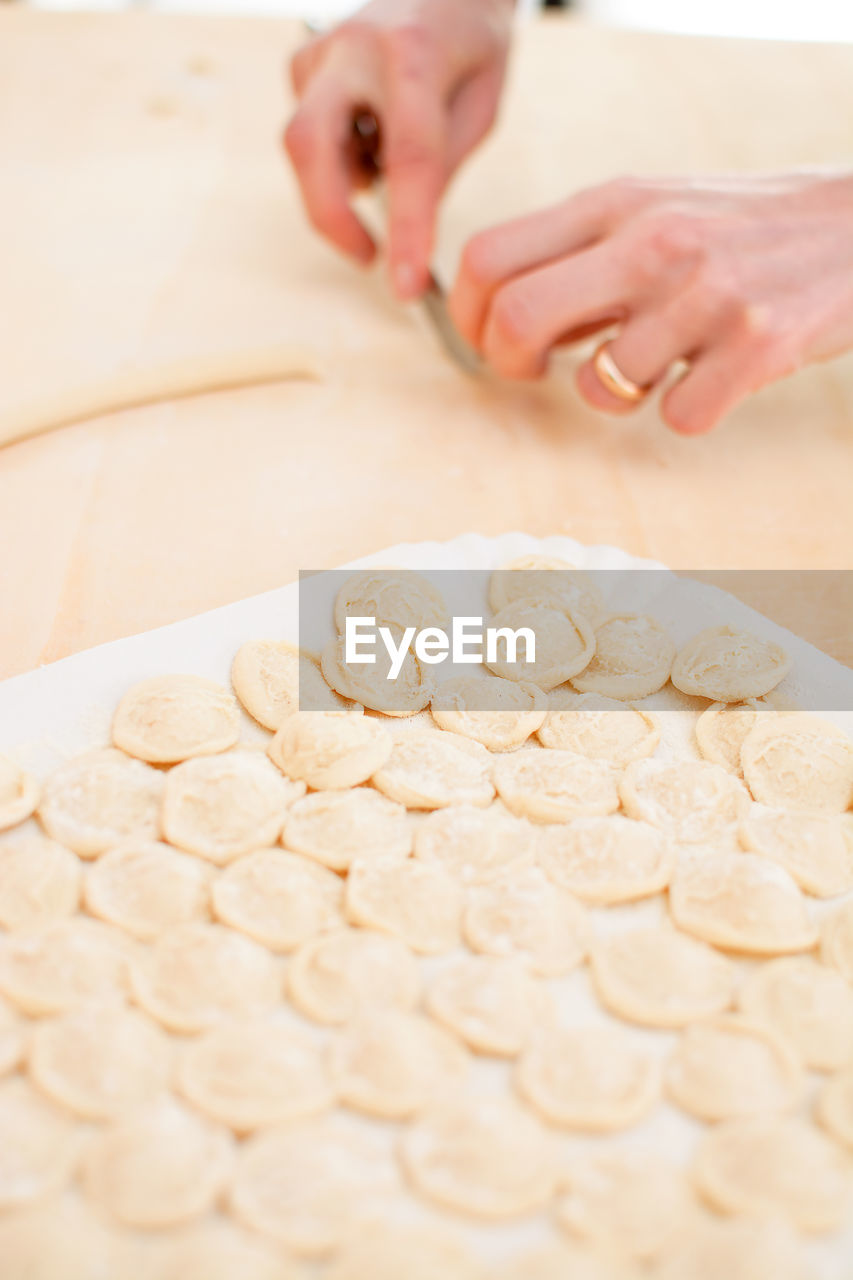 food and drink, food, one person, human hand, indoors, hand, freshness, real people, preparation, selective focus, human body part, dough, women, lifestyles, preparing food, making, holding, raw food, midsection, finger