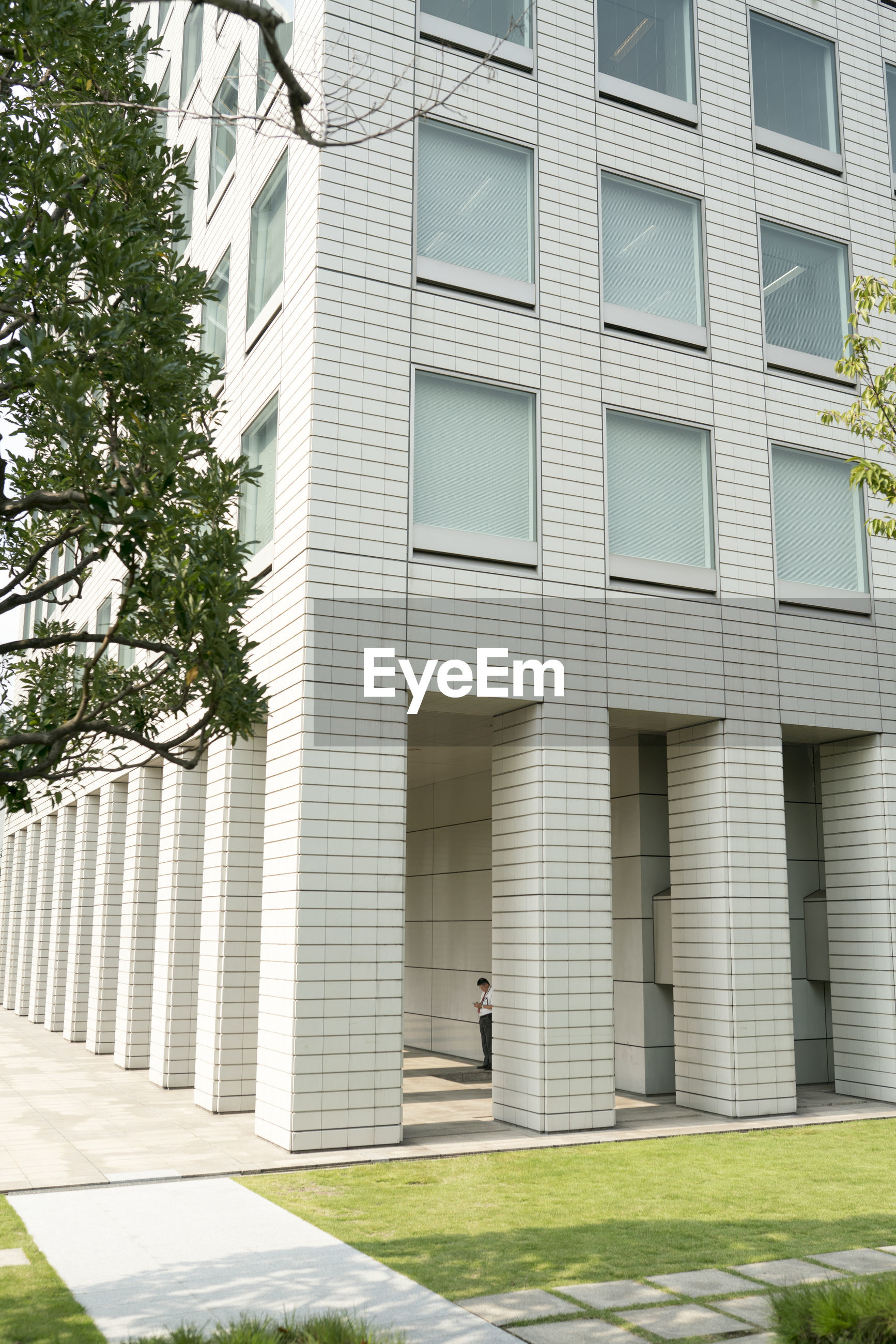 FULL LENGTH OF PERSON WALKING ON MODERN BUILDING
