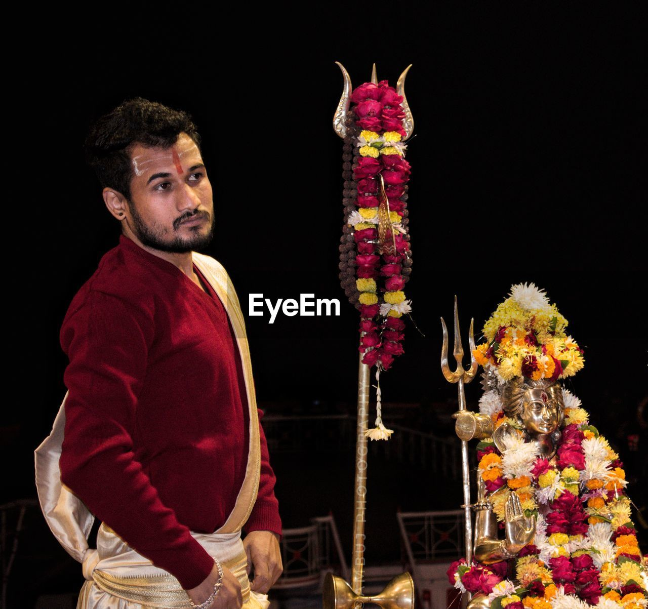 one person, three quarter length, indoors, flower, flowering plant, holding, standing, looking away, front view, studio shot, casual clothing, real people, black background, facial hair, looking, young men, beard, representation, waist up, flower arrangement