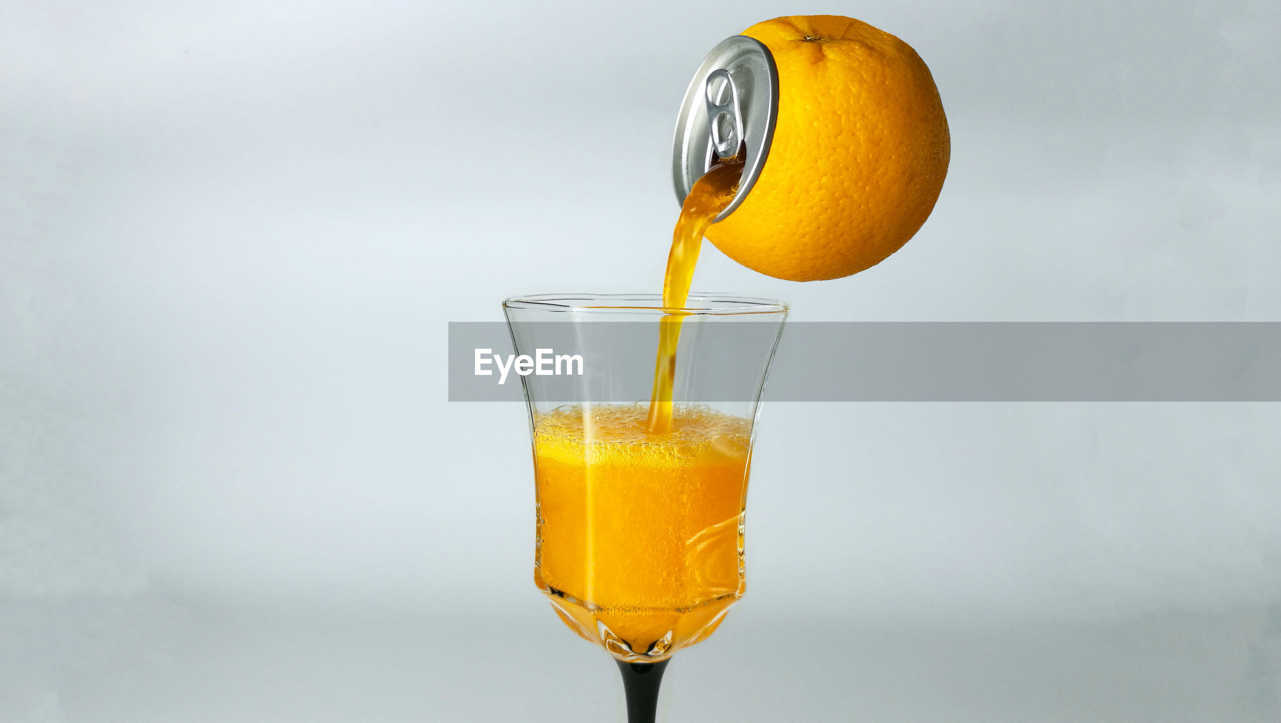 Digital composite image of orange pouring drink in glass