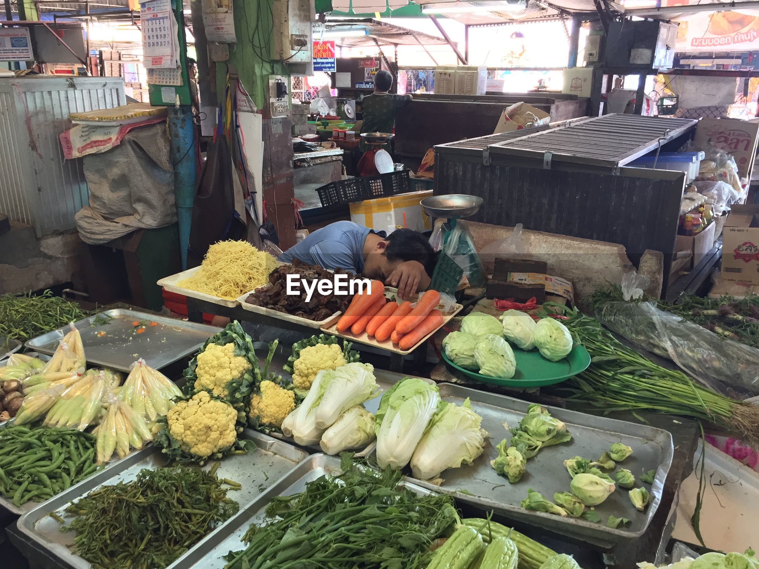 Man sleeping by vegetables at market
