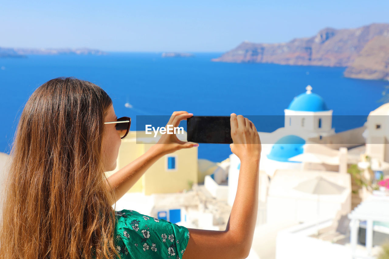 leisure activity, long hair, real people, lifestyles, mobile phone, hairstyle, focus on foreground, photography themes, one person, hair, wireless technology, portrait, technology, women, smart phone, headshot, photographing, sea, rear view, portable information device, fashion, outdoors