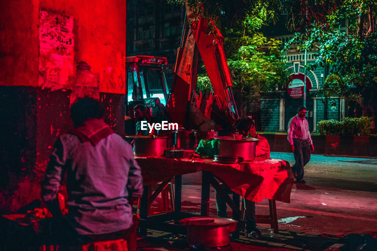 red, real people, table, men, group of people, women, adult, night, people, standing, lifestyles, sitting, seat, restaurant, leisure activity, rear view, built structure, city, business