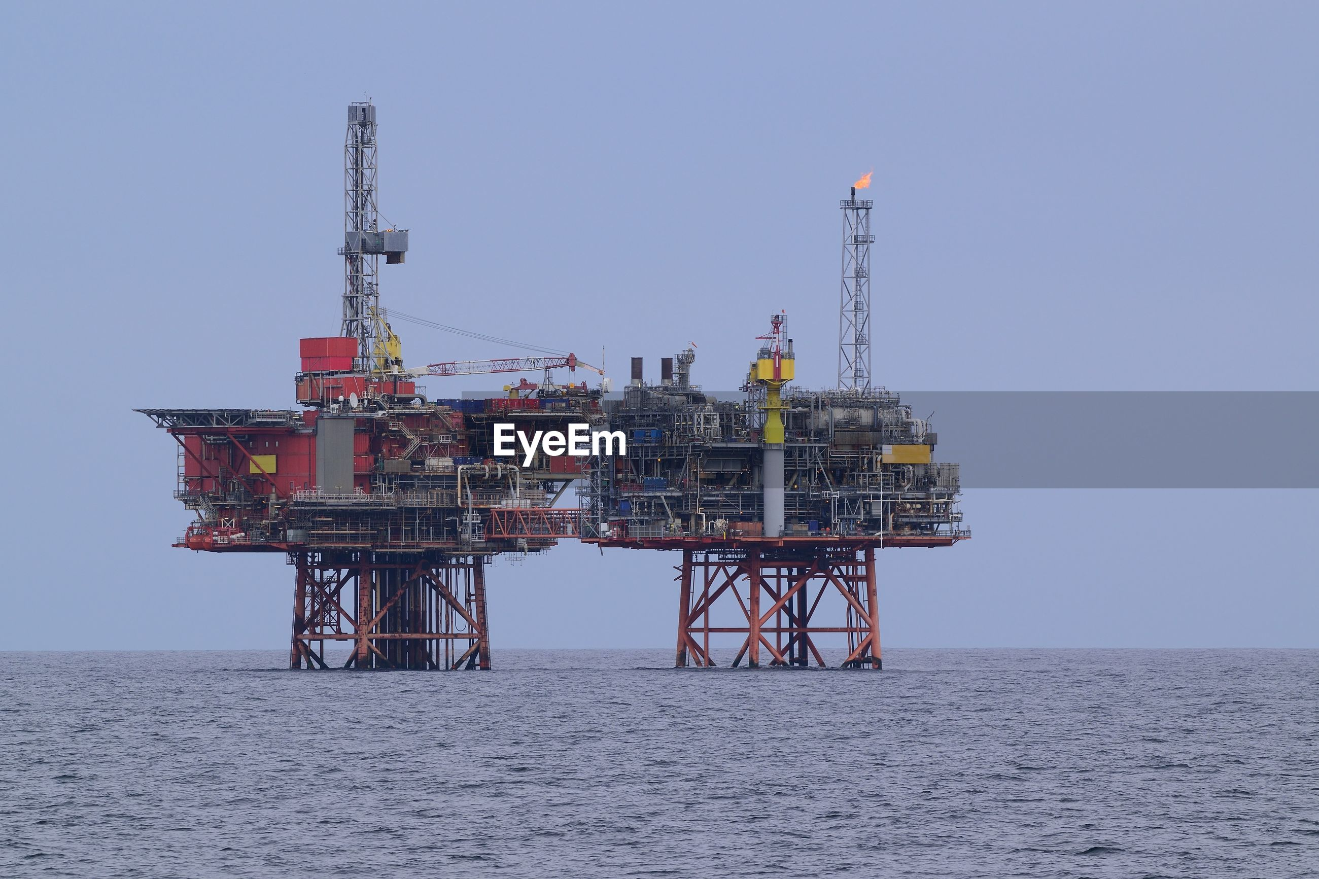 Drilling rig in sea against clear sky