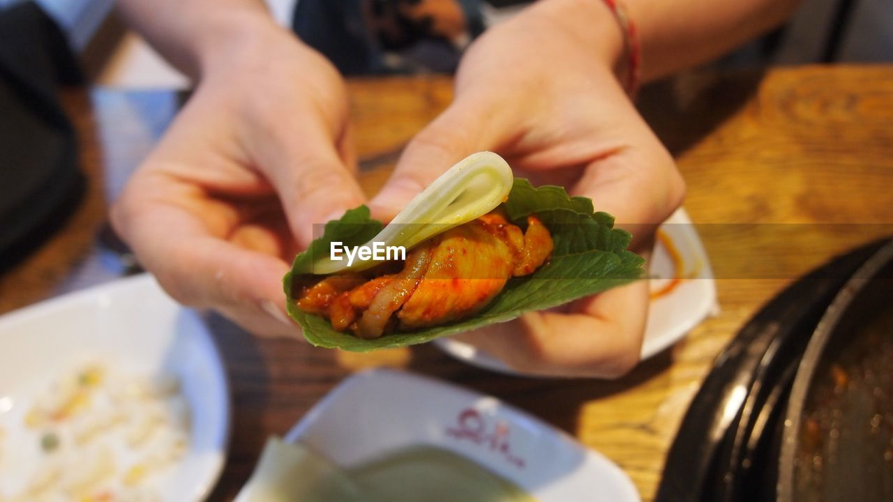 Cropped Hands Holding Food On Table At Restaurant