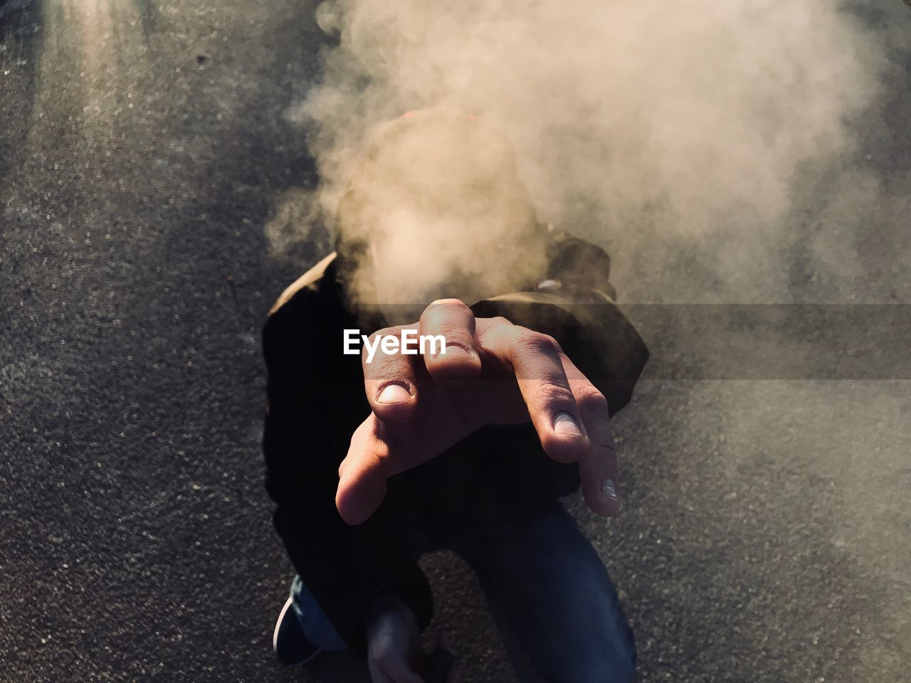 Close-Up Of Man Hand With Smoke Covering Face On Street