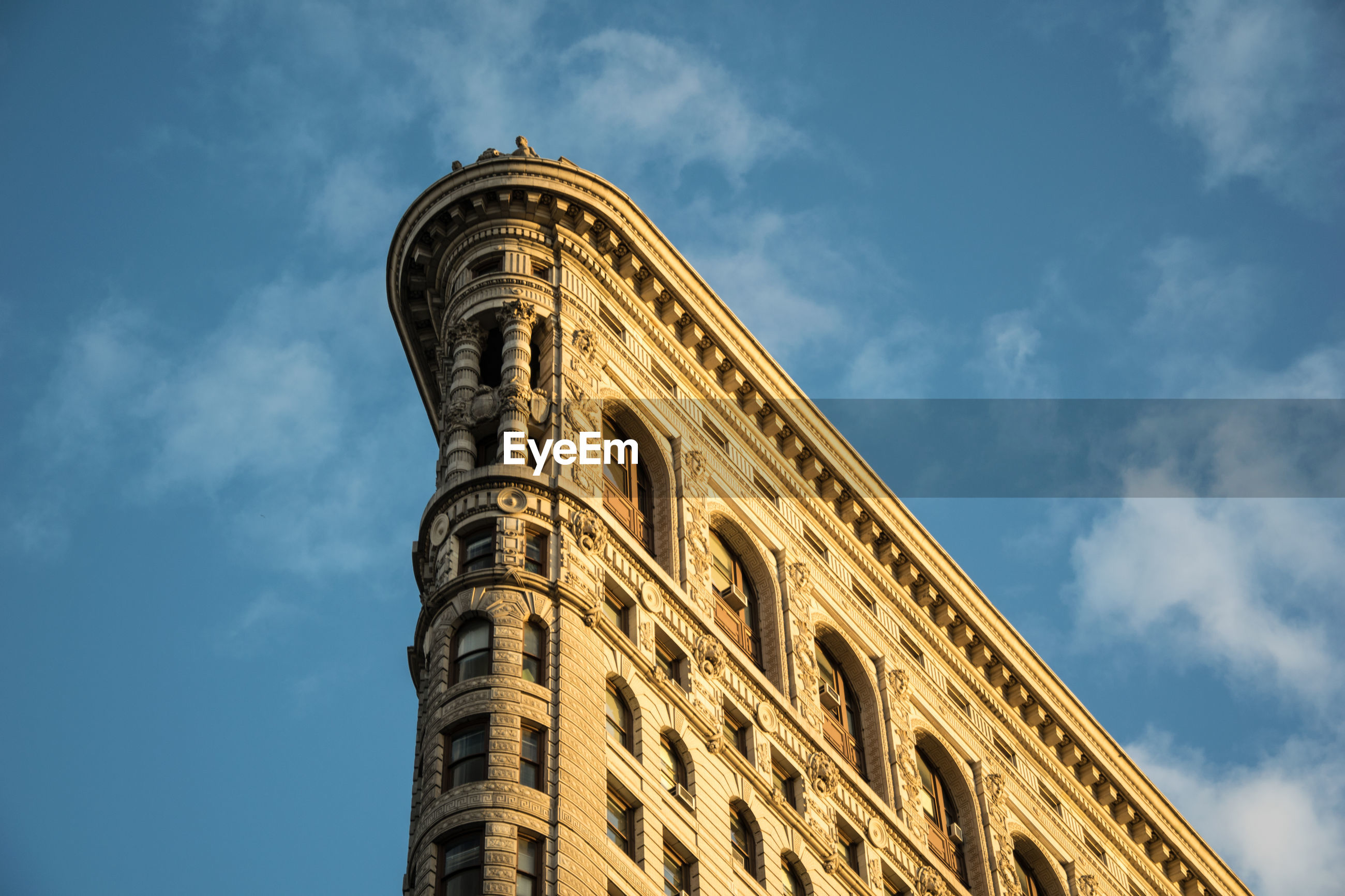 Low angle view of flatiron building against cloudy sky