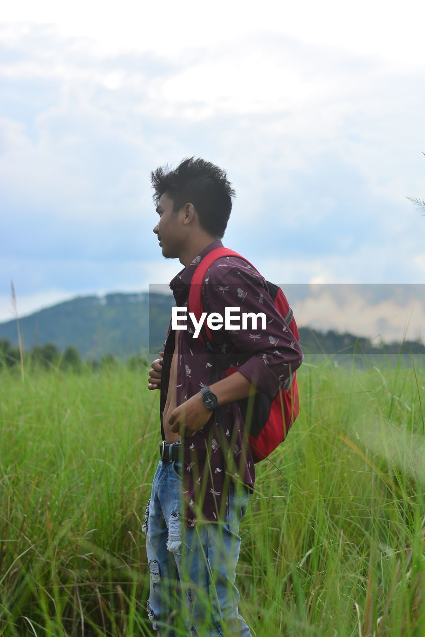 land, field, grass, one person, real people, plant, standing, sky, young adult, leisure activity, casual clothing, three quarter length, lifestyles, nature, side view, landscape, green color, day, outdoors
