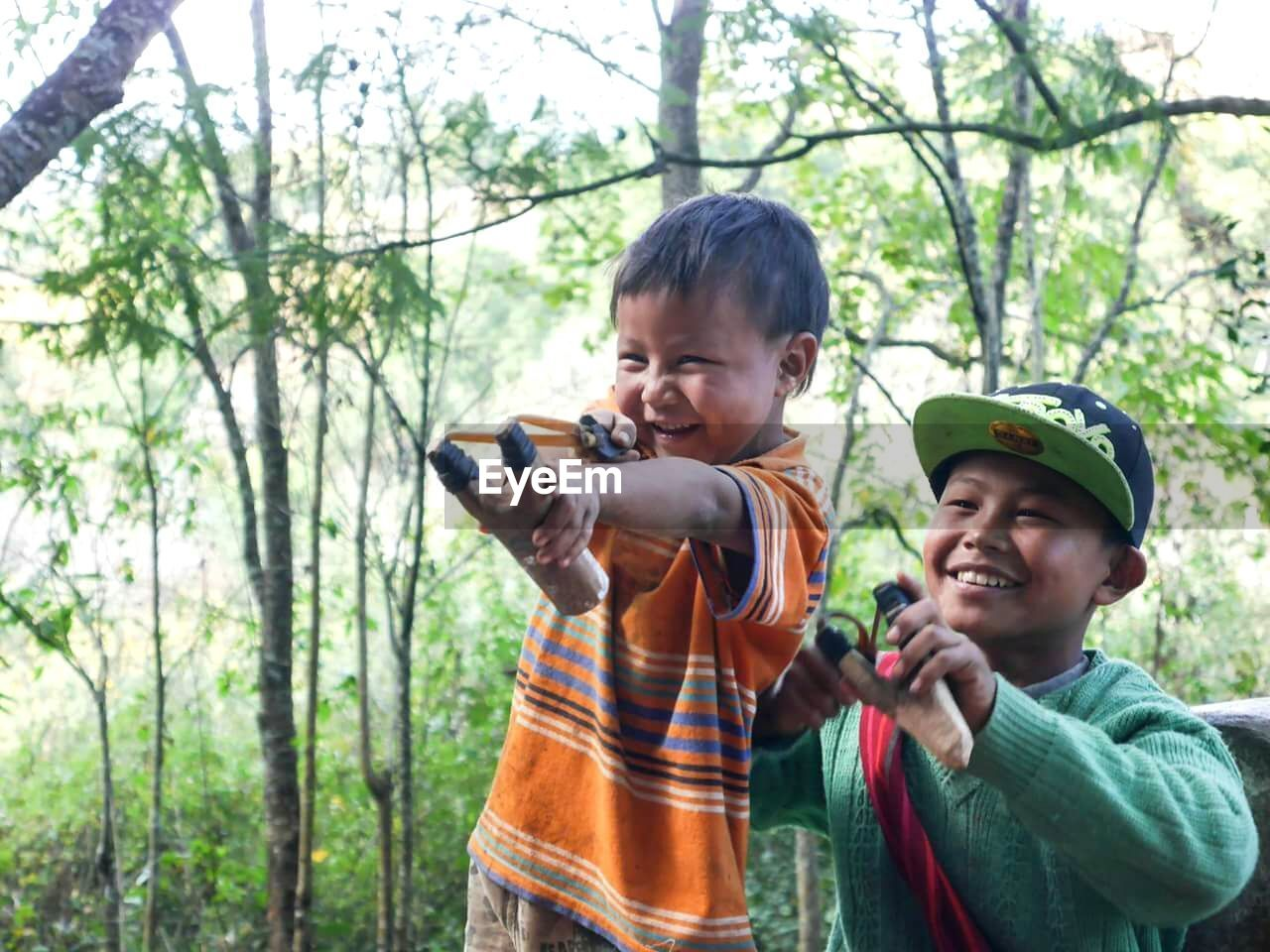 child, boys, childhood, smiling, tree, males, two people, cheerful, family, happiness, forest, fun, son, enjoyment, leisure activity, father, nature, day, bonding, togetherness, outdoors, people, adult, standing, learning, men, rural scene, helmet, camouflage clothing