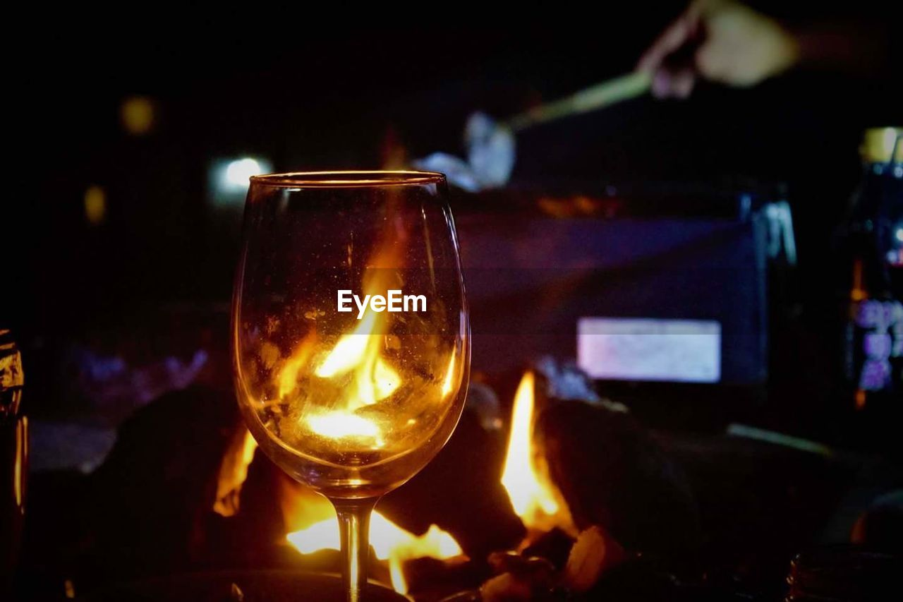 night, flame, heat - temperature, glowing, burning, food and drink, illuminated, focus on foreground, food, no people, wine, indoors, close-up, wineglass, freshness