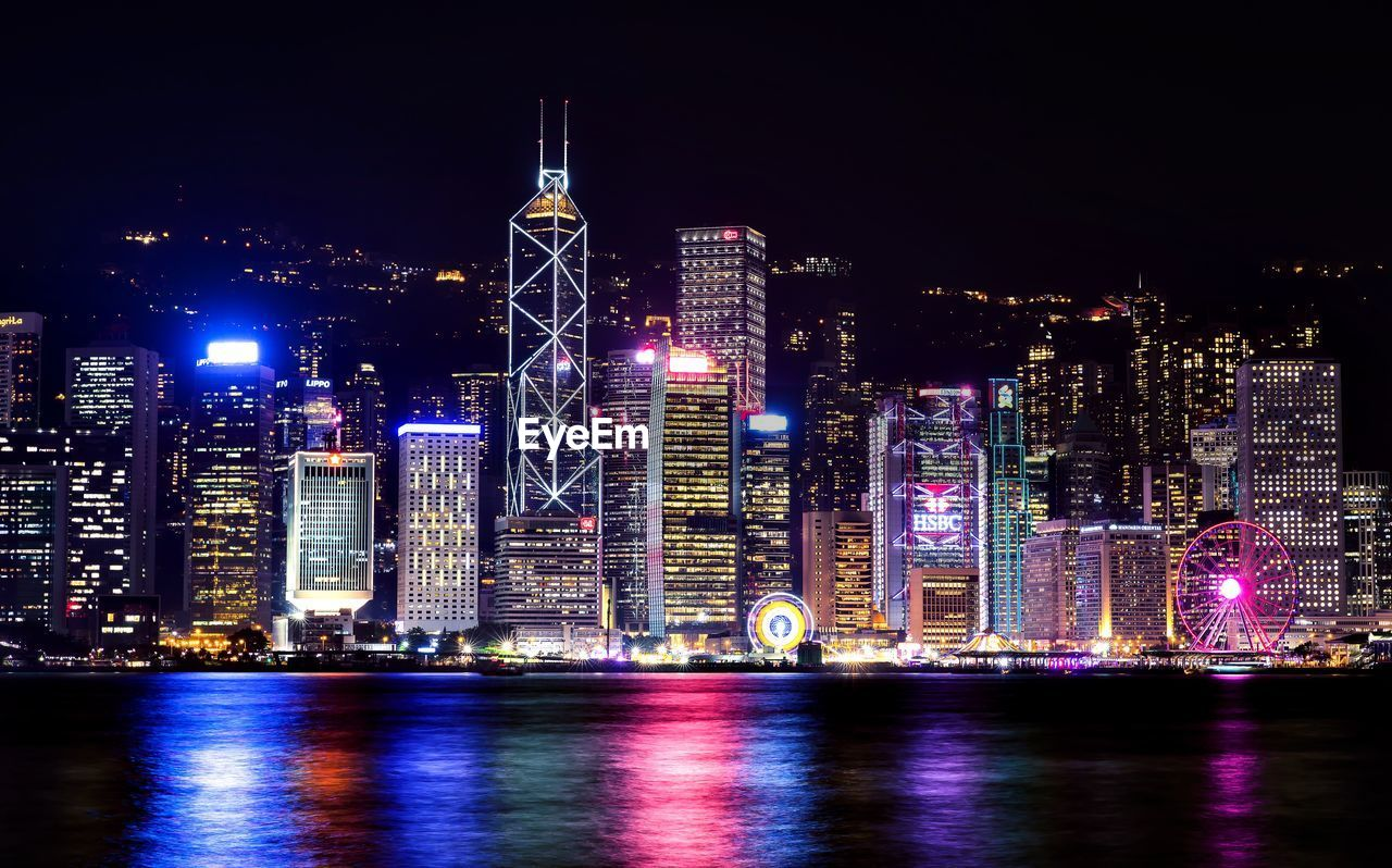 Illuminated victoria harbour - hong kong by river against sky at night