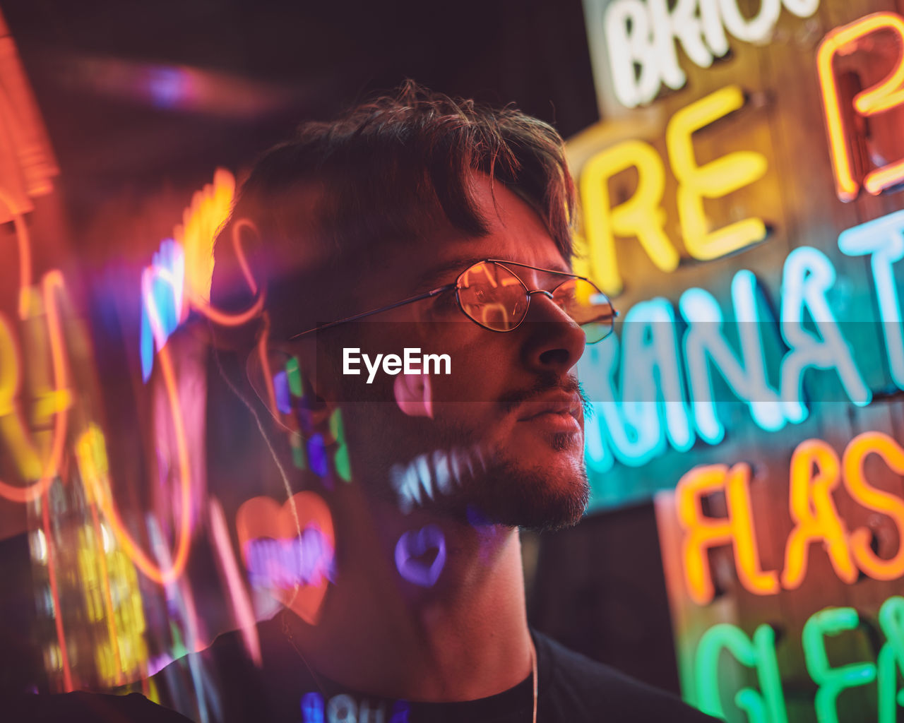 headshot, one person, real people, illuminated, lifestyles, leisure activity, communication, portrait, young adult, text, young men, front view, glasses, night, neon, men, western script, adult, nightlife