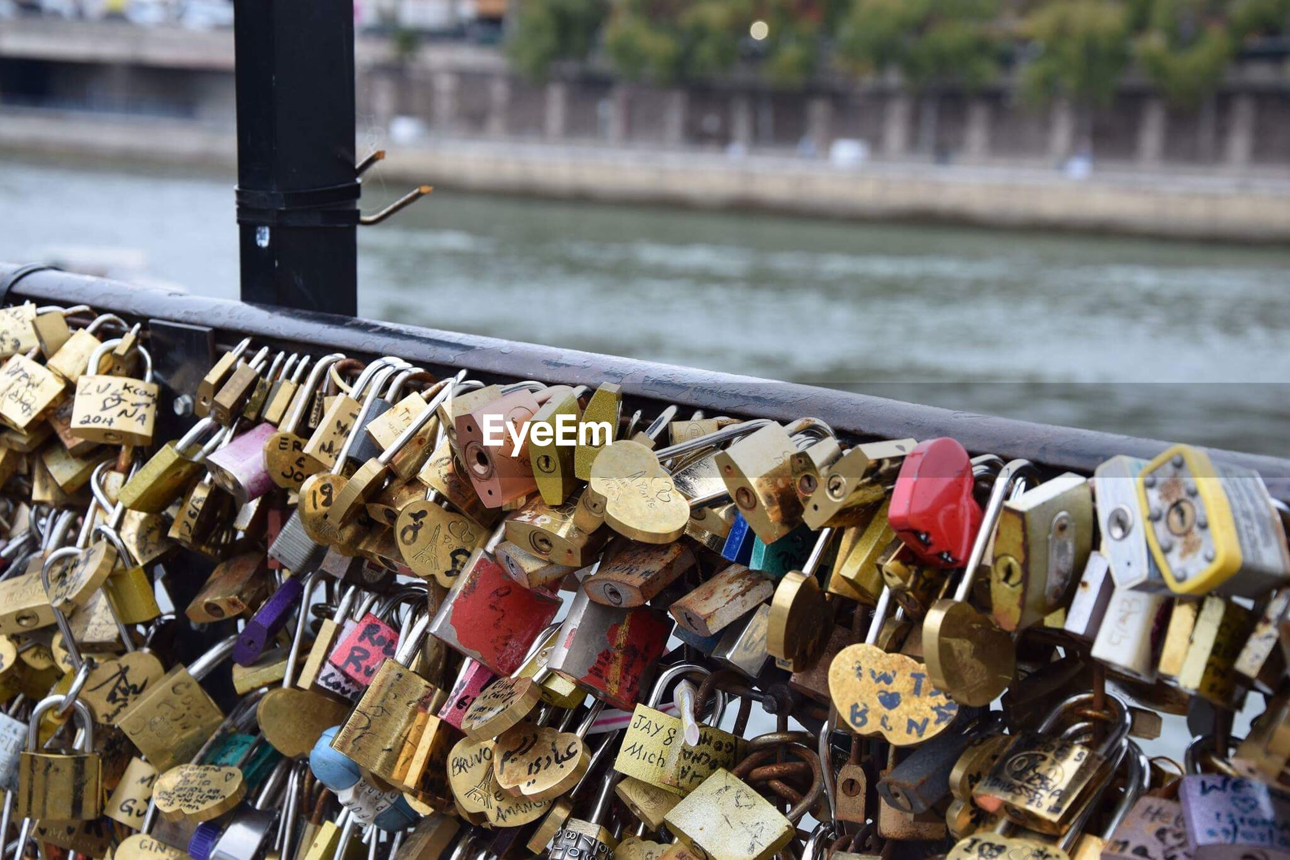 Close-up of padlocks on railing over river