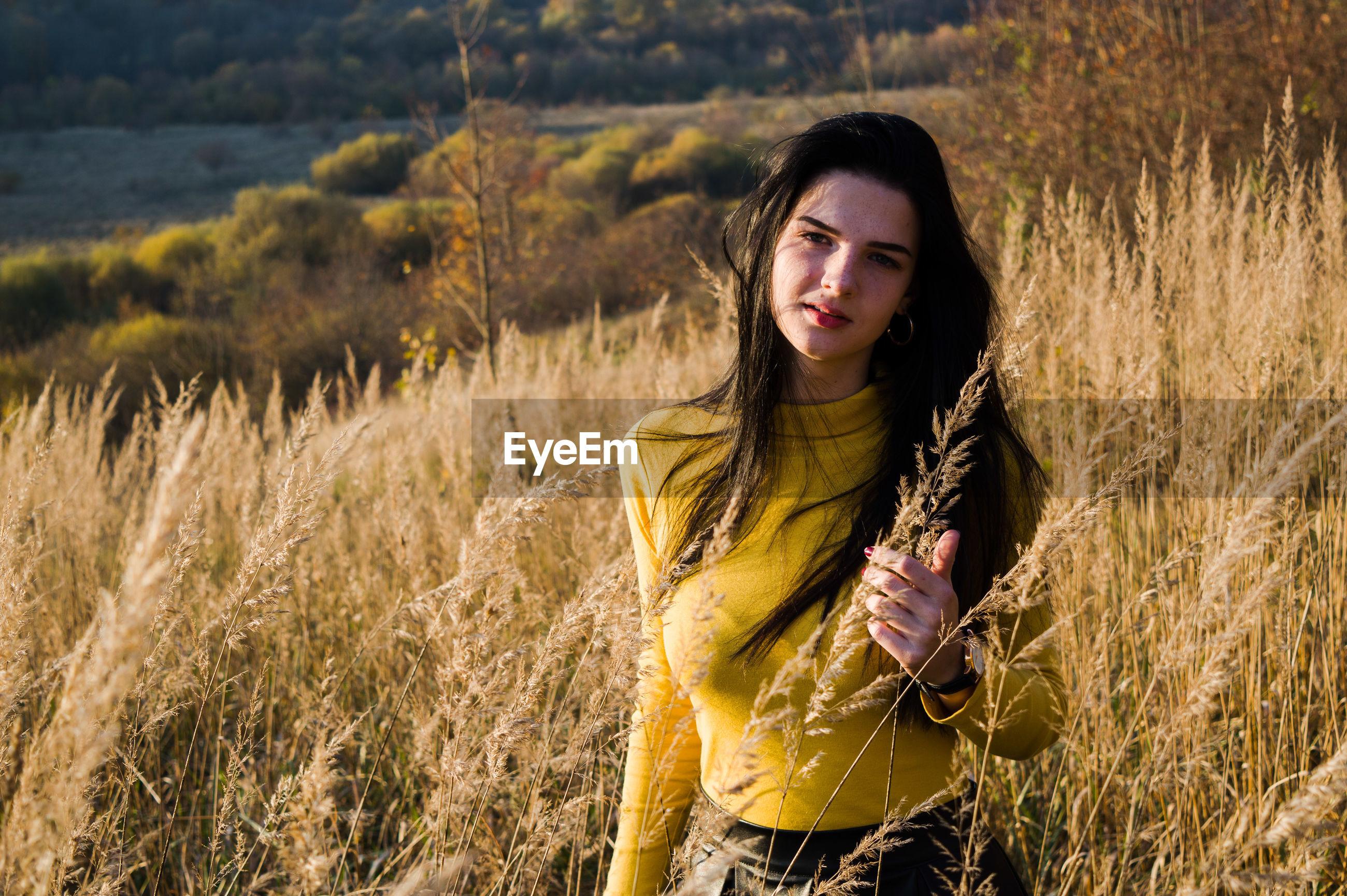 Portrait of beautiful woman amidst plants on field
