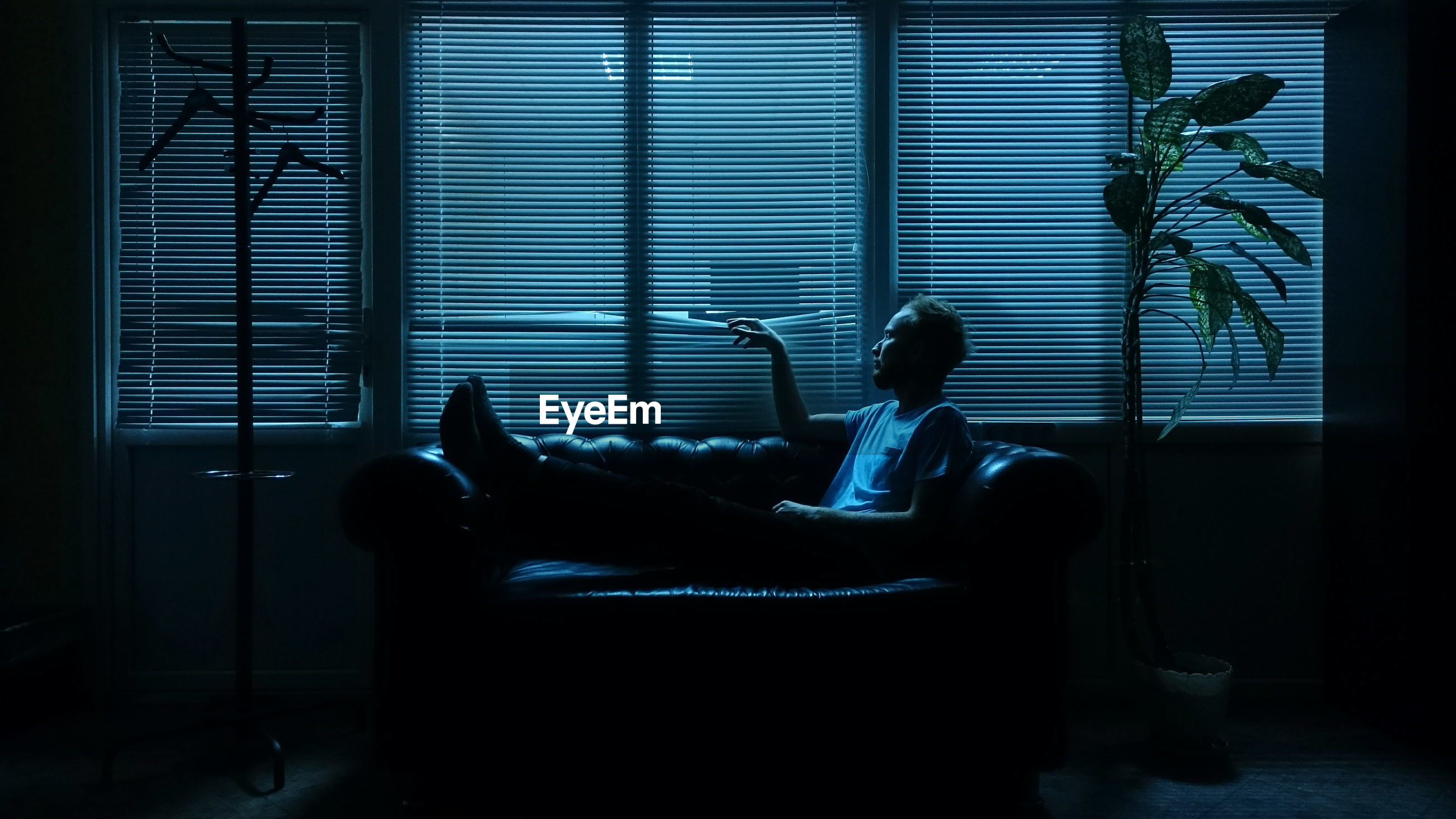 Man relaxing on sofa against window blinds