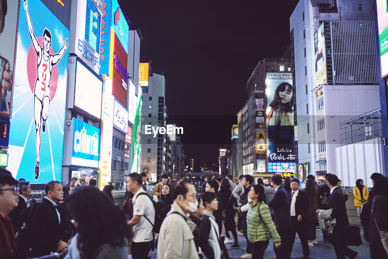 city, group of people, architecture, real people, building exterior, built structure, large group of people, crowd, night, illuminated, men, city life, women, lifestyles, street, adult, walking, advertisement, building