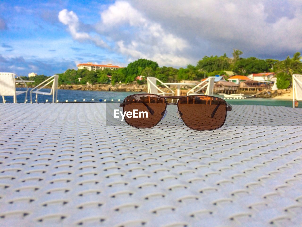 cloud - sky, sky, sunglasses, fashion, architecture, day, glasses, nature, no people, built structure, outdoors, beach, table, chair, building exterior, seat, summer, close-up, sunlight, surface level, swimming pool, personal accessory